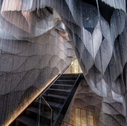 Kengo Kuma drapes Casa Batlló staircase in a sinuous metal chain curtain