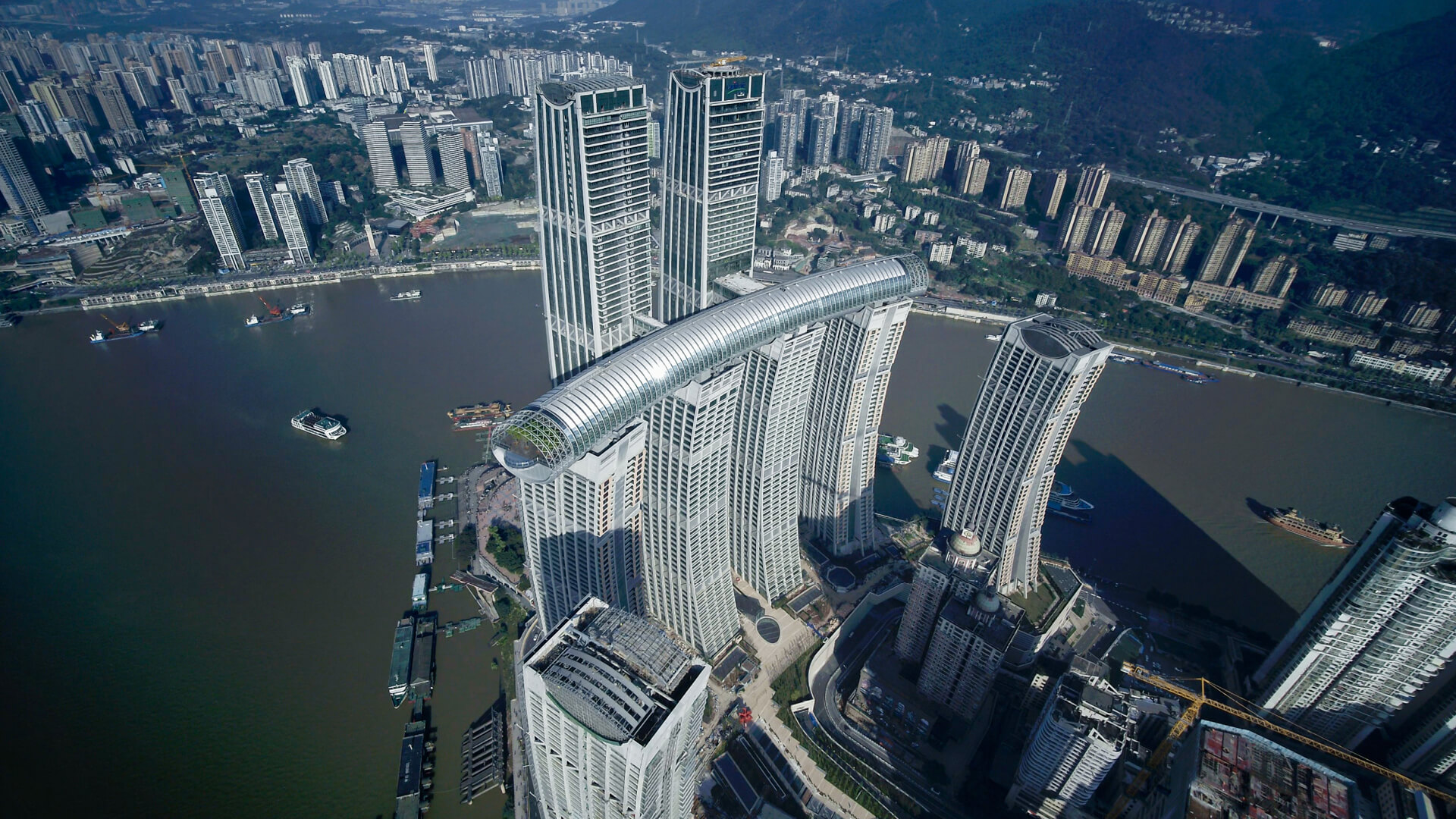 An exterior view of Raffles City Chongqing. The Crystal sky bridge is nestled atop four 250-metre-tall skyscrapers and linked to two adjacent skyscrapers by cantilever bridges | Raffles City Chongqing |  Safdie Architects | China | STIRworld