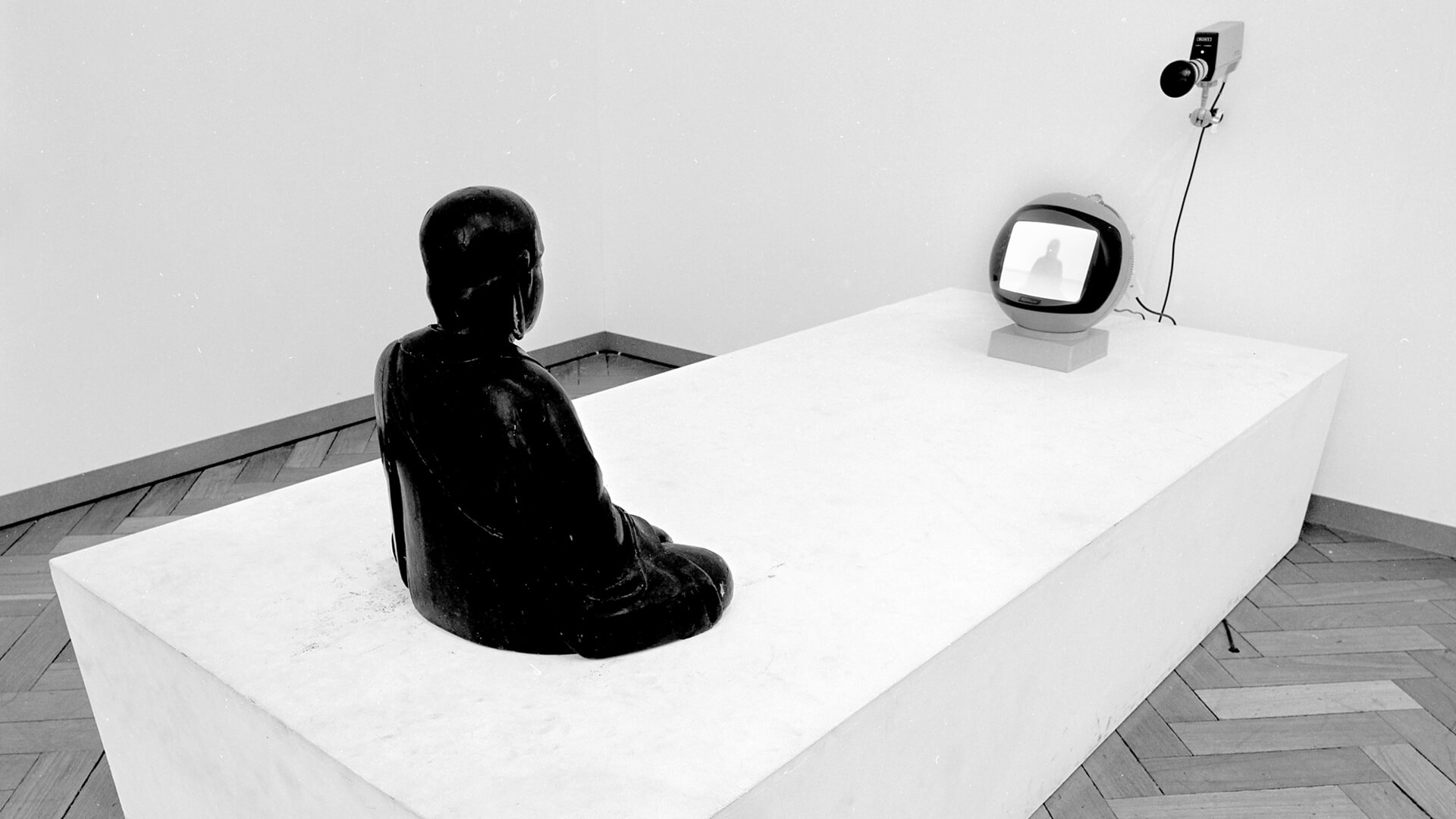 An image of 'TV-Buddha' from Nam June Paik's debut solo exhibition at Stedelijk Museum in 1977 | The Future Is Now by Nam June Paik | STIRworld
