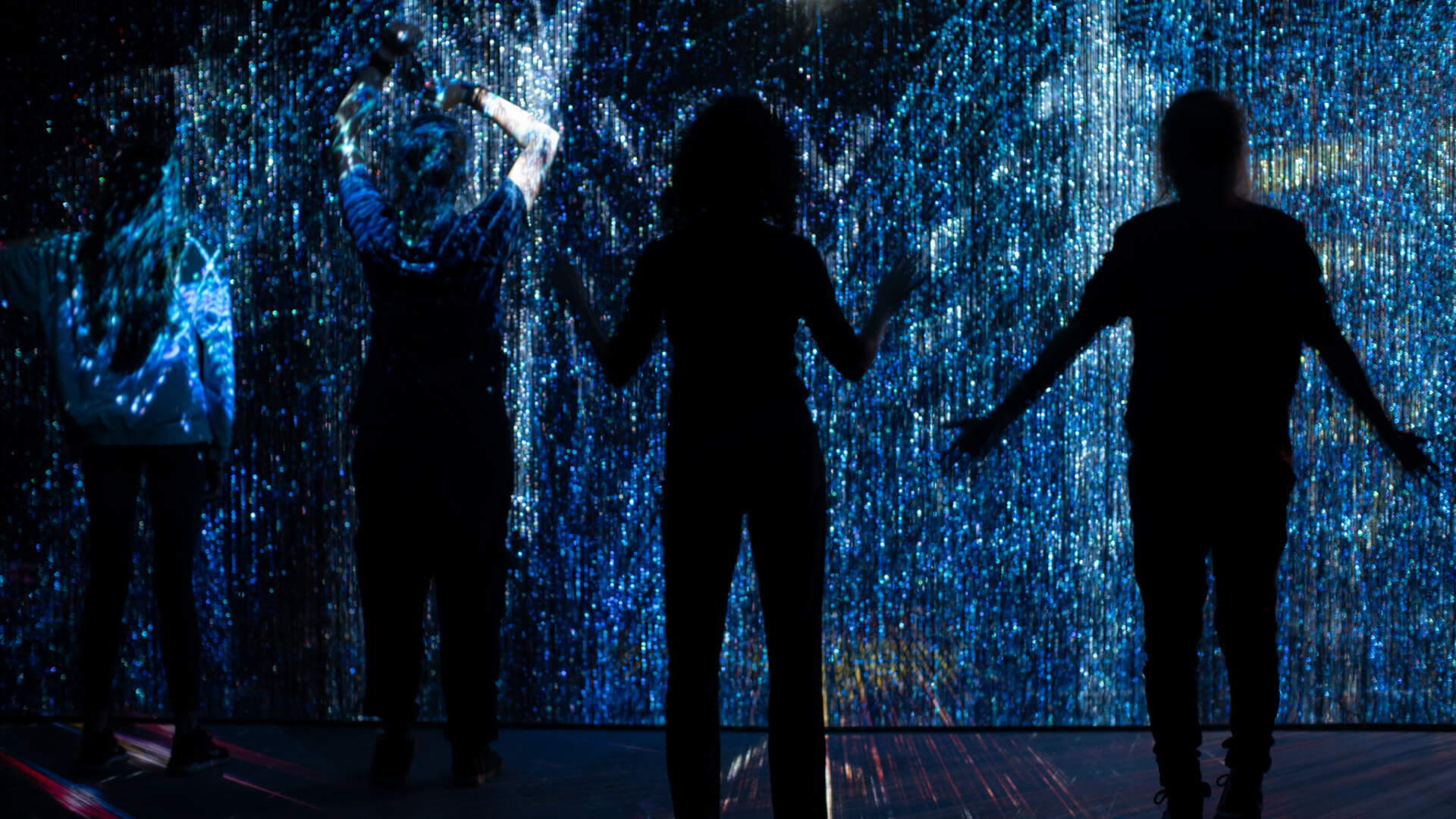 Viewers stand before the artwork and play with the AI responsive technology | We Are All Made of Light| Maja Petric | STIRworld