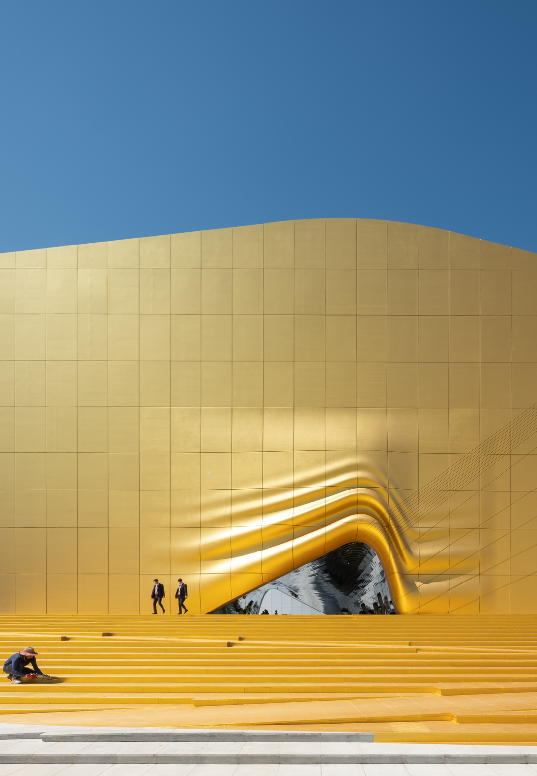 The entrance to The Imprint appears as if it were lifted like a curtain while a gold spotlight were lighting up its steps | The Imprint | MVRDV | STIR