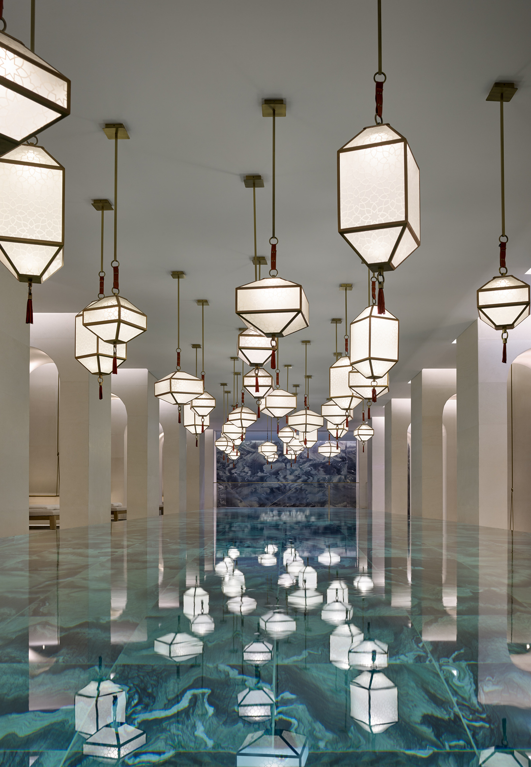 The indoor pool enjoys the attention of glowing lanterns hanging at various heights above it | Four Seasons Kuwait | Yabu Pushelberg | George Yabu, Glenn Pushelburg | STIR