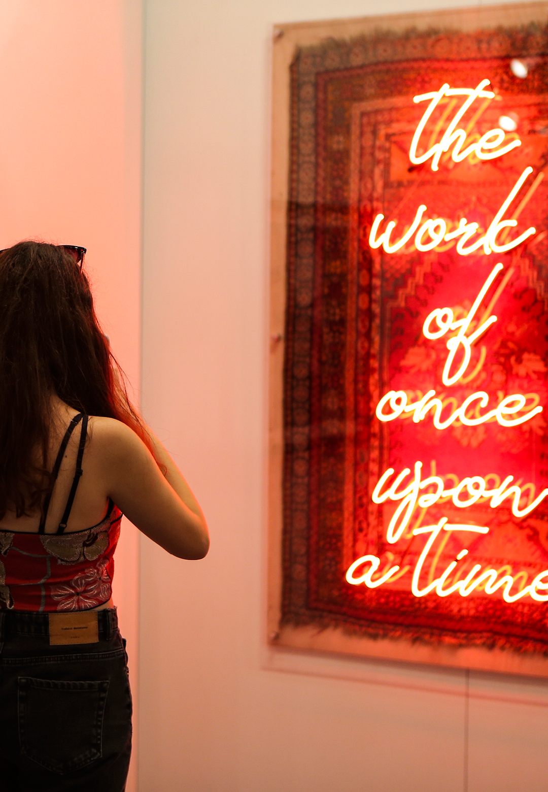 A viewer at the Contemporary Istanbul art fair takes in the light sculpture that juxtaposes a traditional carpet with funky neon text | Contemporary Istanbul | STIR