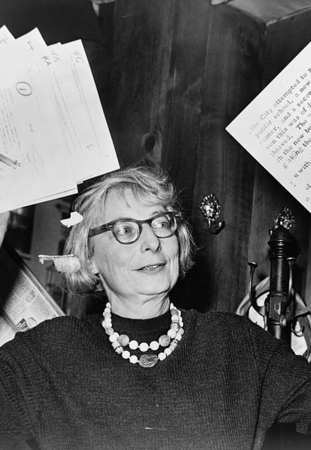 Jane Jacobs, chairman of the committee to save the West Village holds up documentary evidence at press conference at Lions Head Restaurant at Hudson & Charles Sts. (1961) | Jane Jacobs | STIRworld