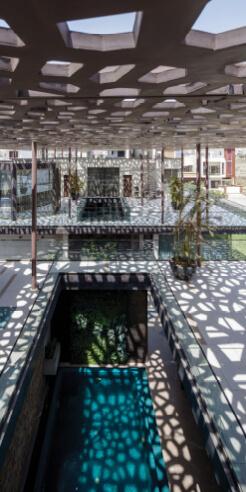 A latticed roof rains dappled light into House Under Shadows by ZED Lab