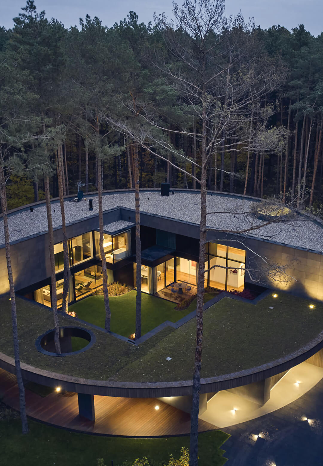 Aerial view of Circle Wood—a house that appears to be carved out of a tree trunk, nestled within a pine forest | Circle Wood by Mobius Architekci in Warsaw | STIRworld