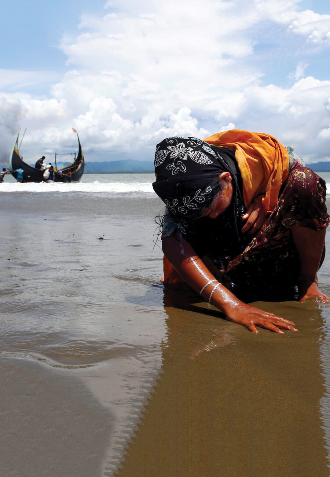 An exhausted Rohingya refugee woman touches the shore after crossing the Bangladesh-Myanmar border by boat through the Bay of Bengal, in Shah Porir Dwip, Bangladesh September 11, 2017| Danish Siddiqui | STIRworld