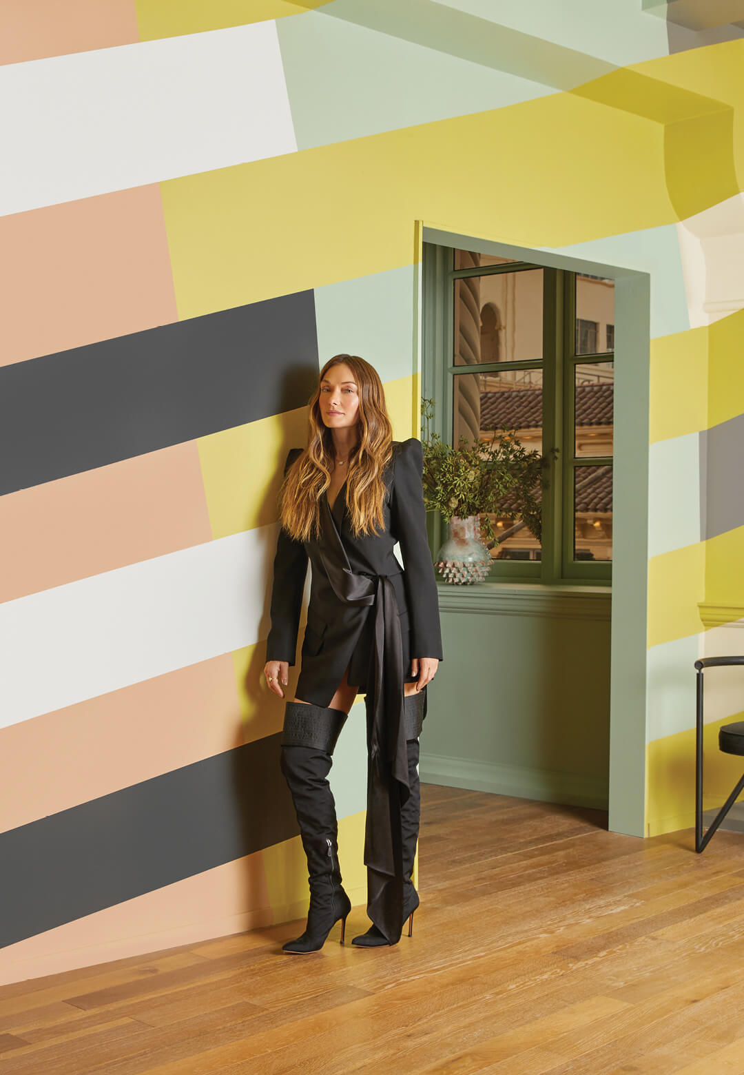 Interior designer Kelly Wearstler stands against a colour block wall showcasing the eight shades of the California Collection she created in partnership with Farrow & Ball | California Collection | Kelly Wearstler X Farrow & Ball | STIRworld