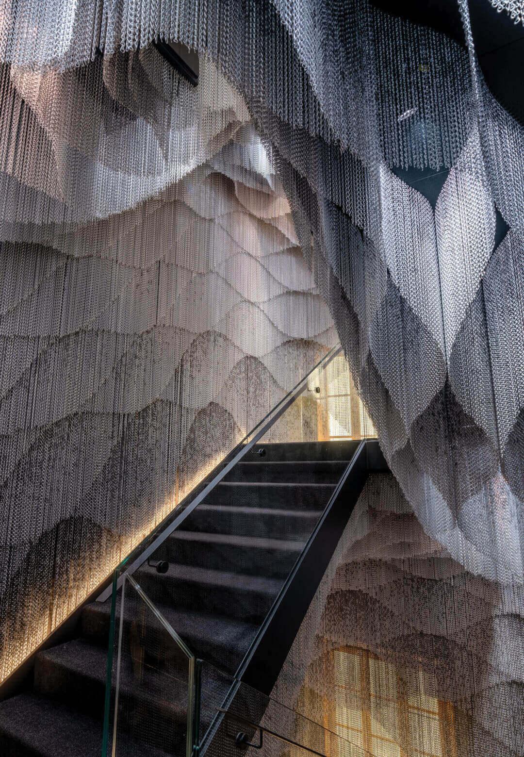 Kengo Kuma and Associates has draped a staircase of Antoni Gaudí's Casa Batlló in an aluminium link curtain | Casa Batlló Staircase by Kengo Kuma | STIRworld