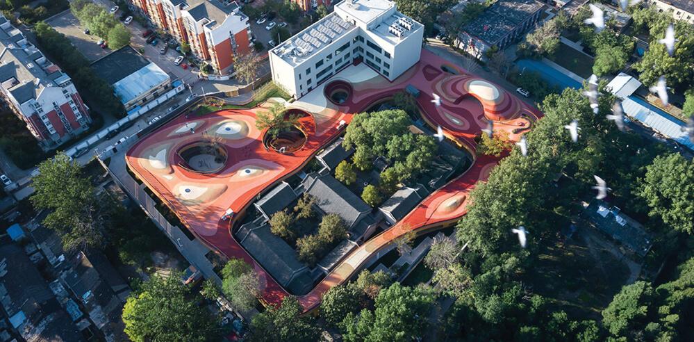 An orange rooftop playground swirls atop MAD's YueCheng Courtyard Kindergarten