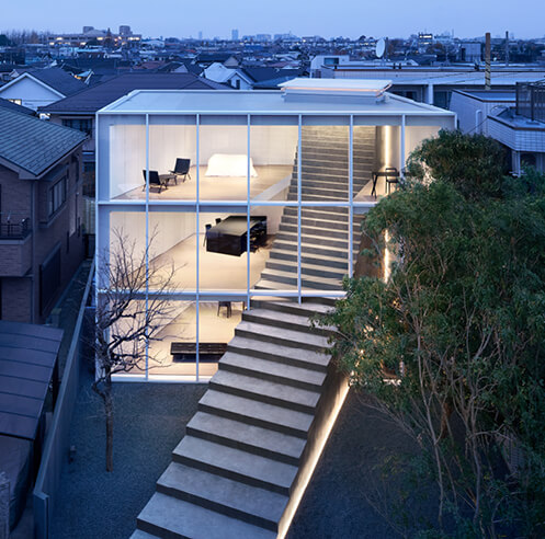 Nendo cuts a sweeping staircase through the facade of a two-family home in Tokyo