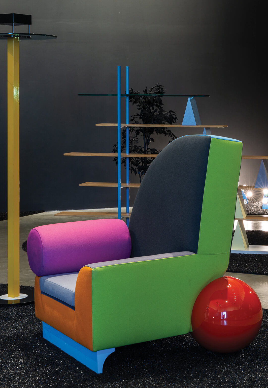 Installation view with King floor lamp (1983) by Ettore Sottsass and Bel Air armchair (1982) by Peter Shire in the foreground at Memphis: Plastic View, MK Gallery, Milton Keyes  Memphis: Plastic View   MK Gallery   STIRworld