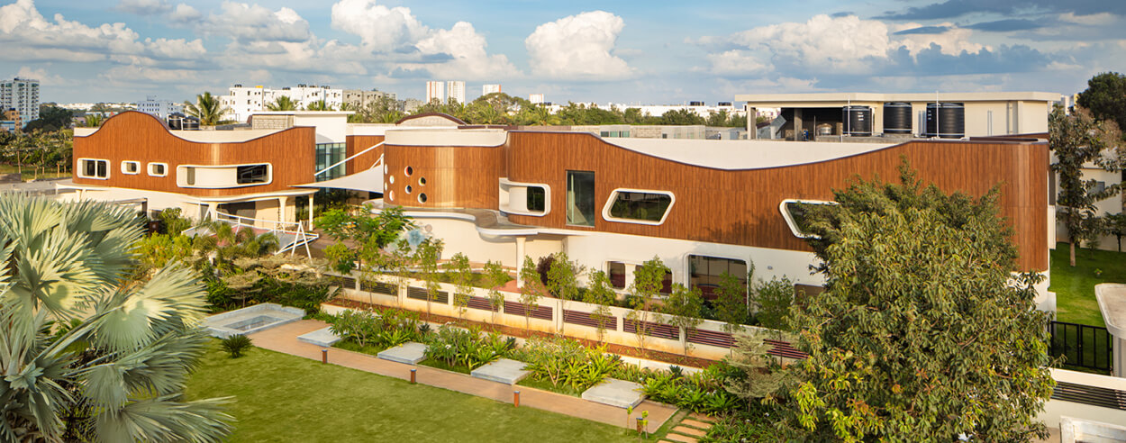 Wooden interiors, open spaces and curved façade shape a Montessari school in India