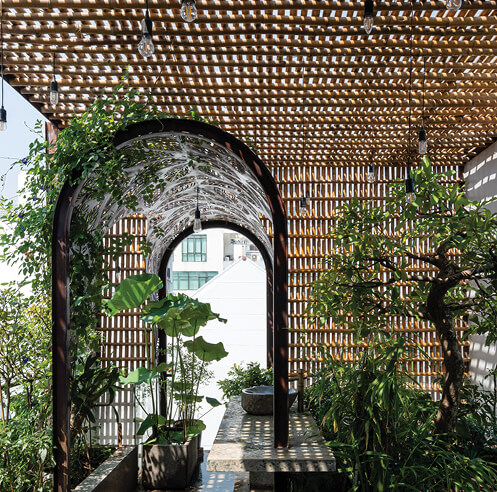 Woven bamboo sticks clad Floating Nest, a narrow Vietnamese house by atelier NgNg