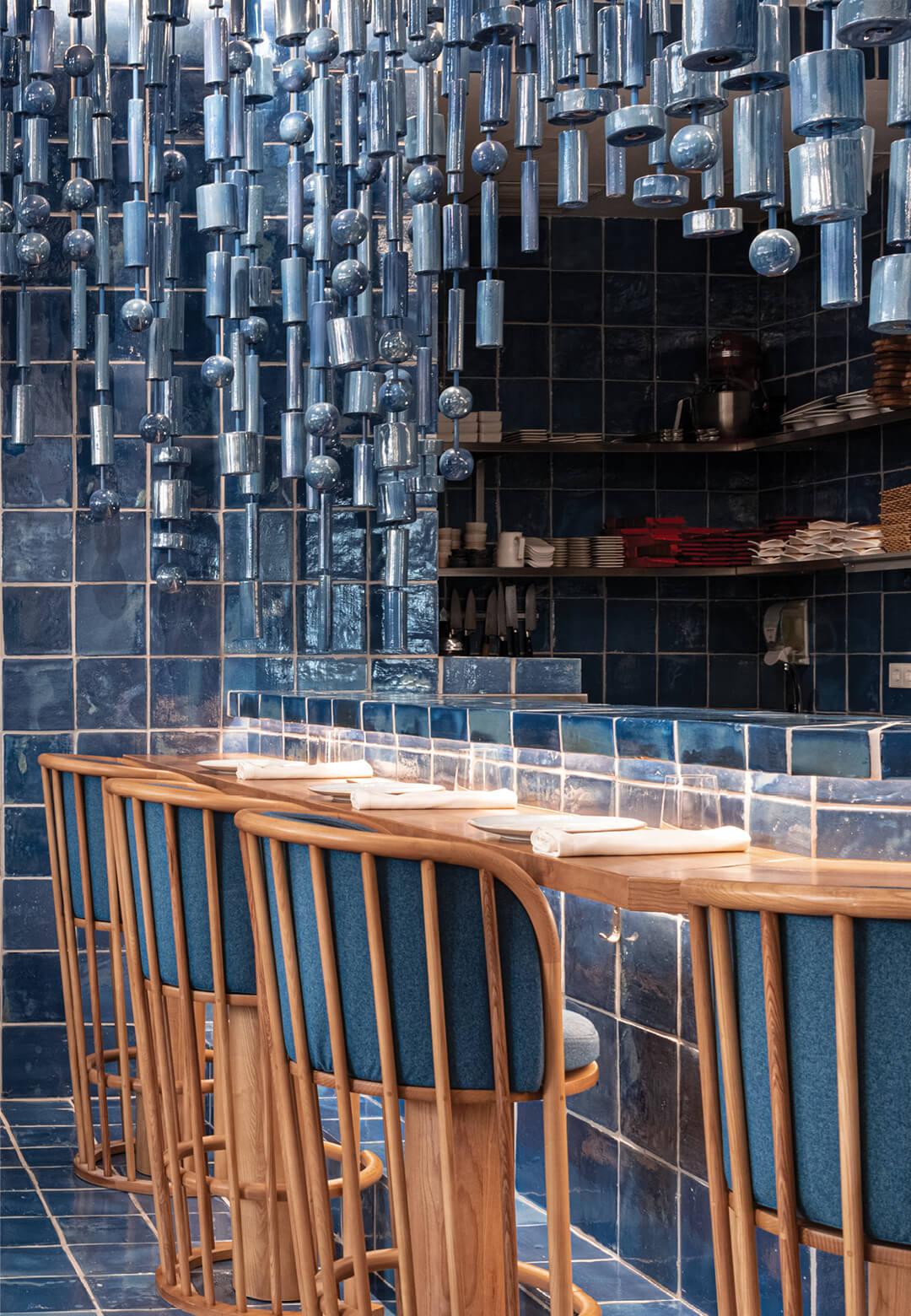 A wavy, sculptural installation made of ceramic hangs inside La Sastrería restaurant in Valencia | La Sastrería bar and restaurant designed by Masquespacio | STIRworld