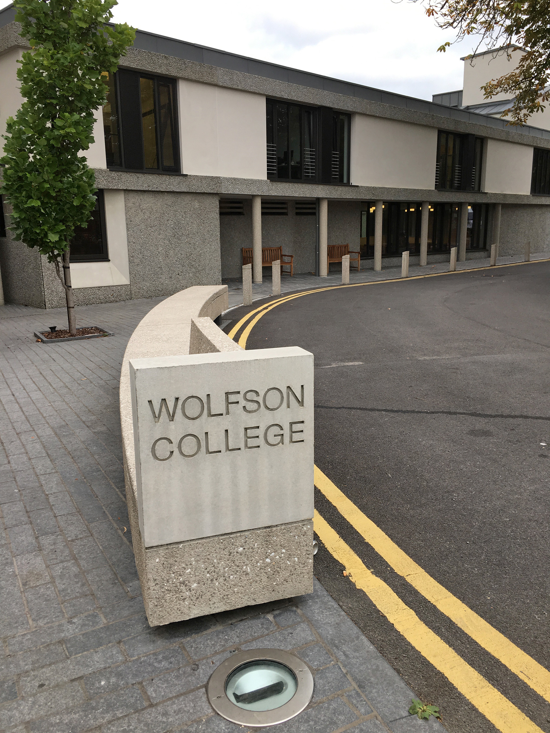 The entrance to the college, a modest low-level sign, curving into a seat for the weary Linton road traveller | Modernity in/as Heritage – The architecture of Wolfson College, Oxford | Amit Khanna | STIR