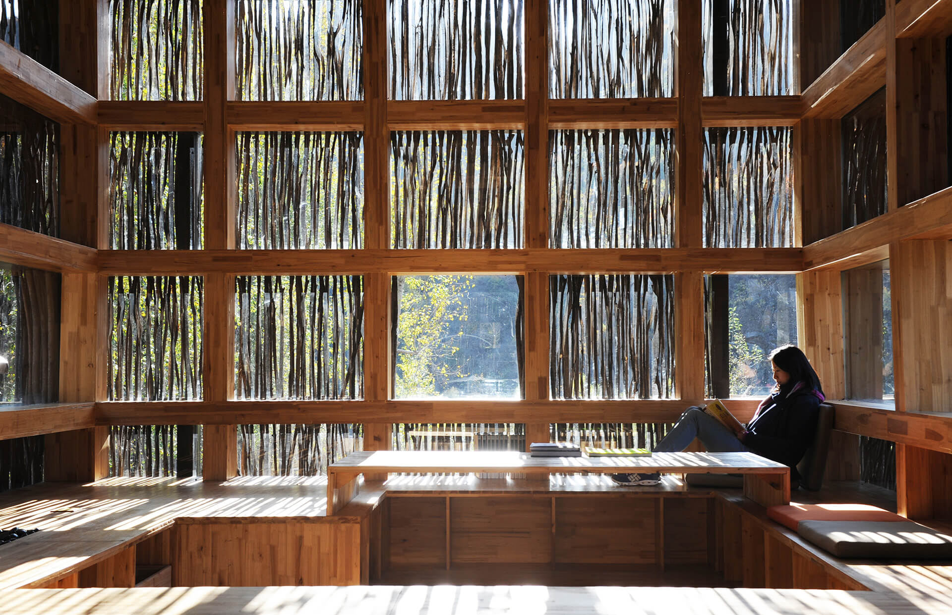 The library with fully glazed interior contains quiet and contemplative reading spaces and a series of platforms which integrate shelving for books | Li Xiadong | STIRworld