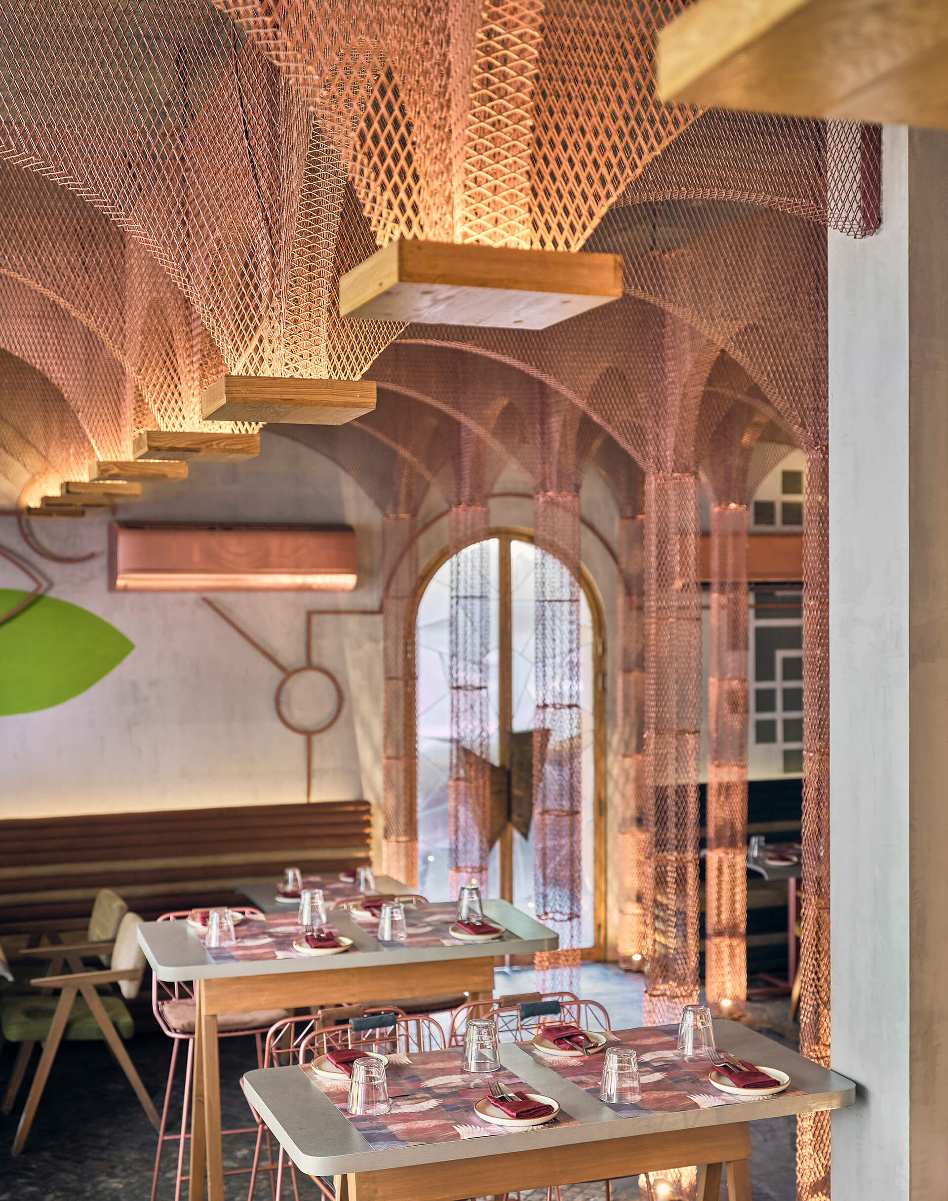 Copper mesh arches hanging from below the ceiling | Bengaluru, India | FADD Studio | STIRworld