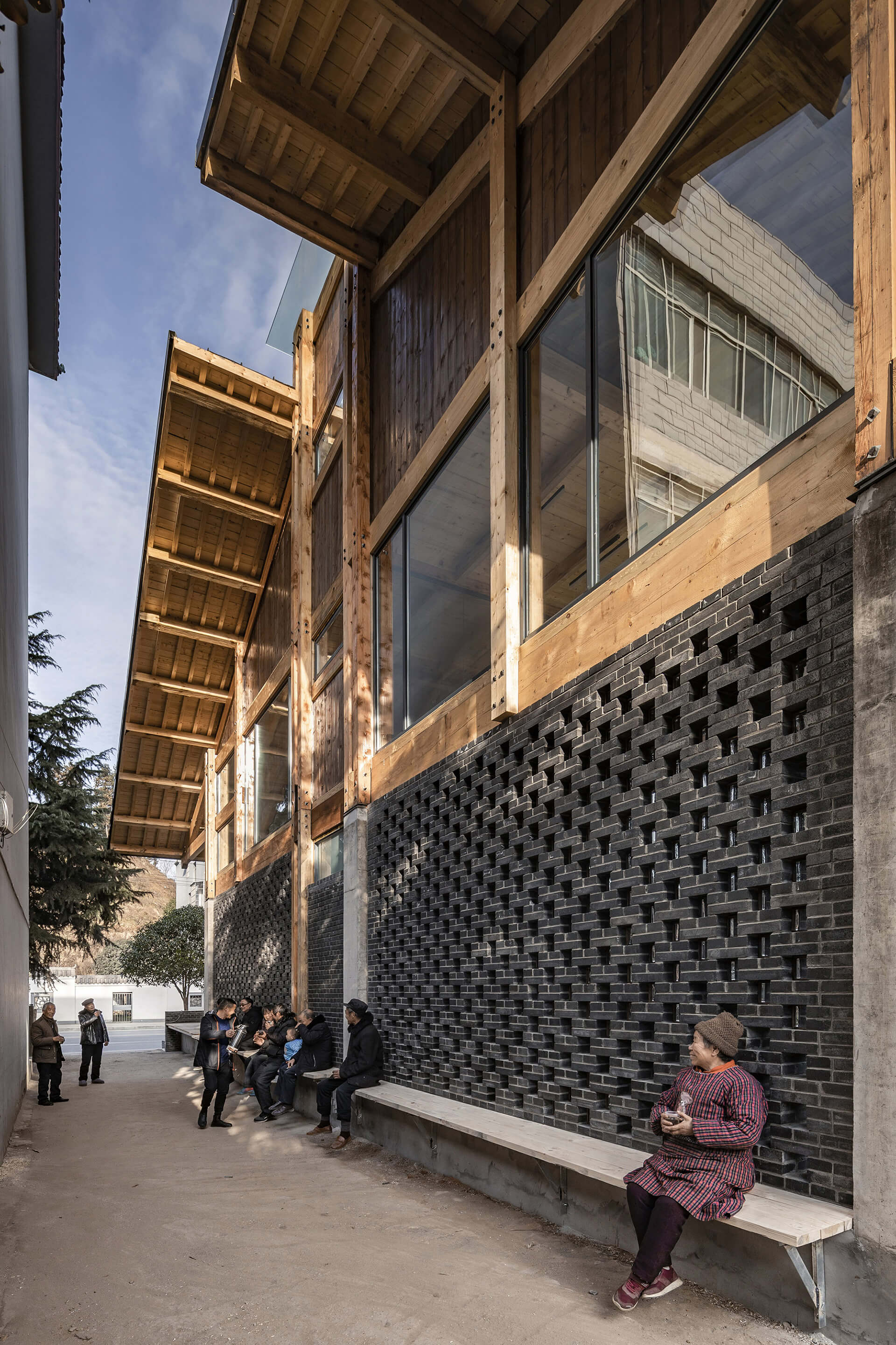 Villagers resting on the wooden bench running along the building's west side | Party and Public Service Center of Yuanheguan Village by LUO Studio | STIRworld