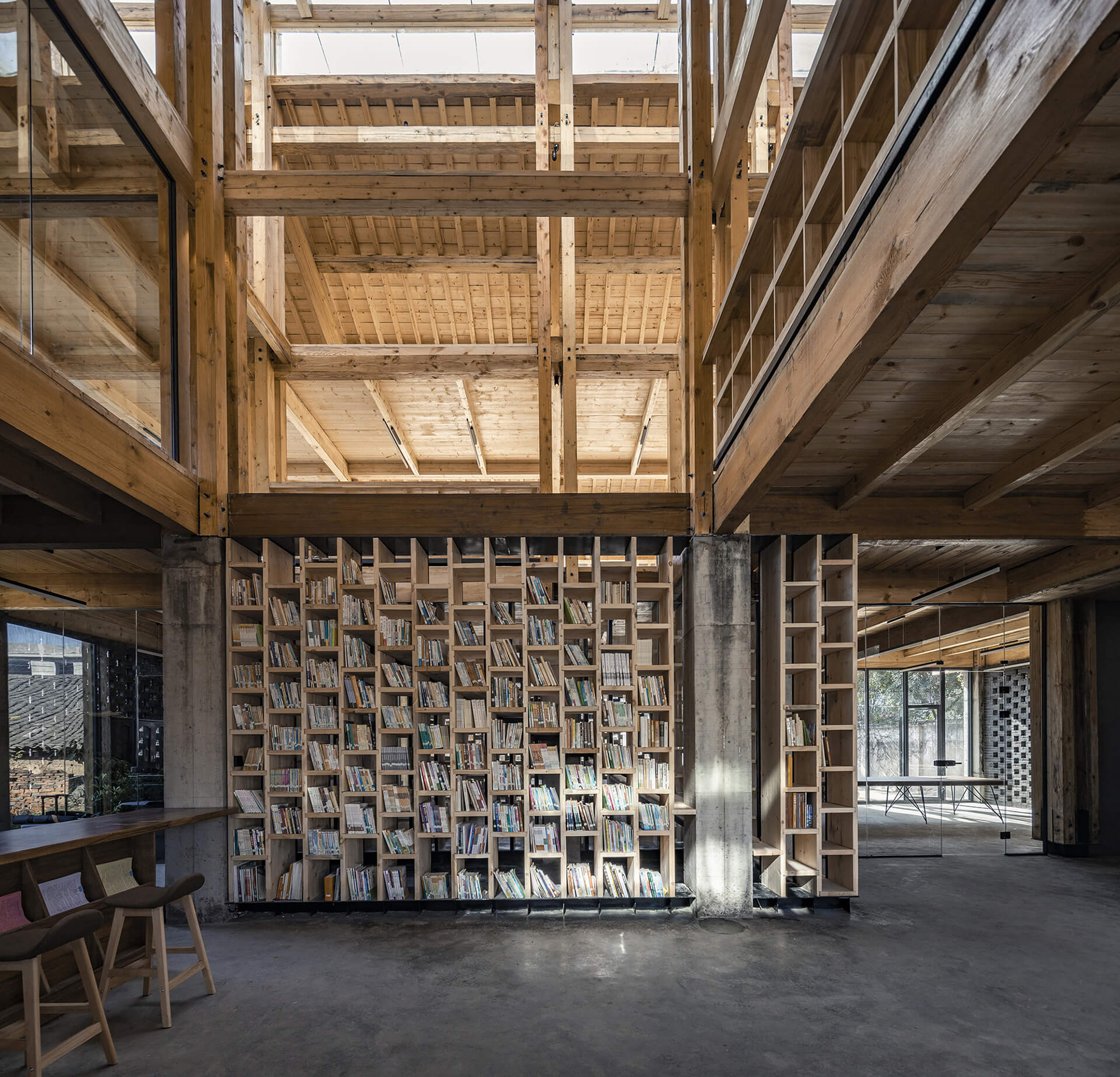 Resting area with a bookshelf dividing the space | Party and Public Service Center of Yuanheguan Village by LUO Studio | STIRworld