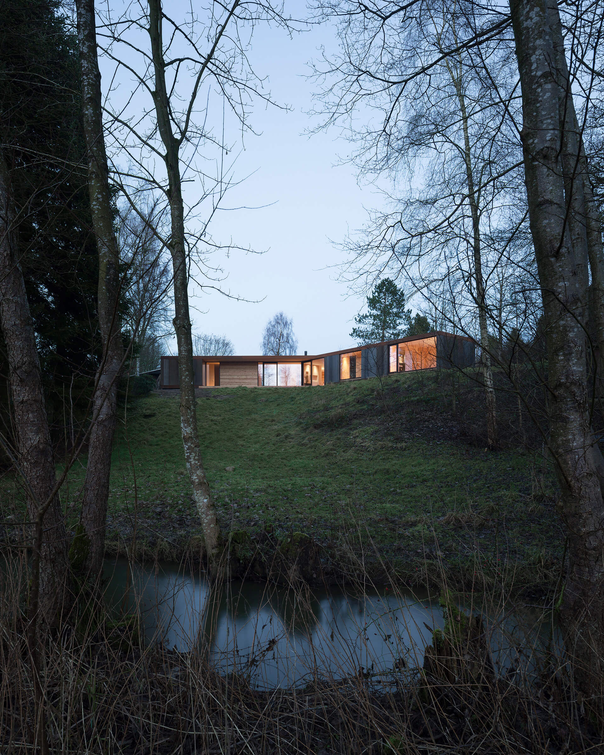 The prefab home Villa Korup rests upon Danish landscape with lofty trees for company | Villa Korup designed by Jan Henrik Jansen Arkitekter with Marshall Blecher | STIRworld