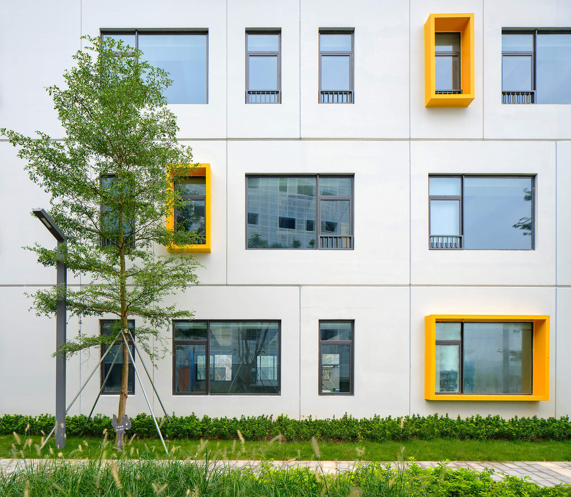 Protruding yellow metal frame openings on selected windows | Crossboundaries | Shenzhen, China | STIRworld