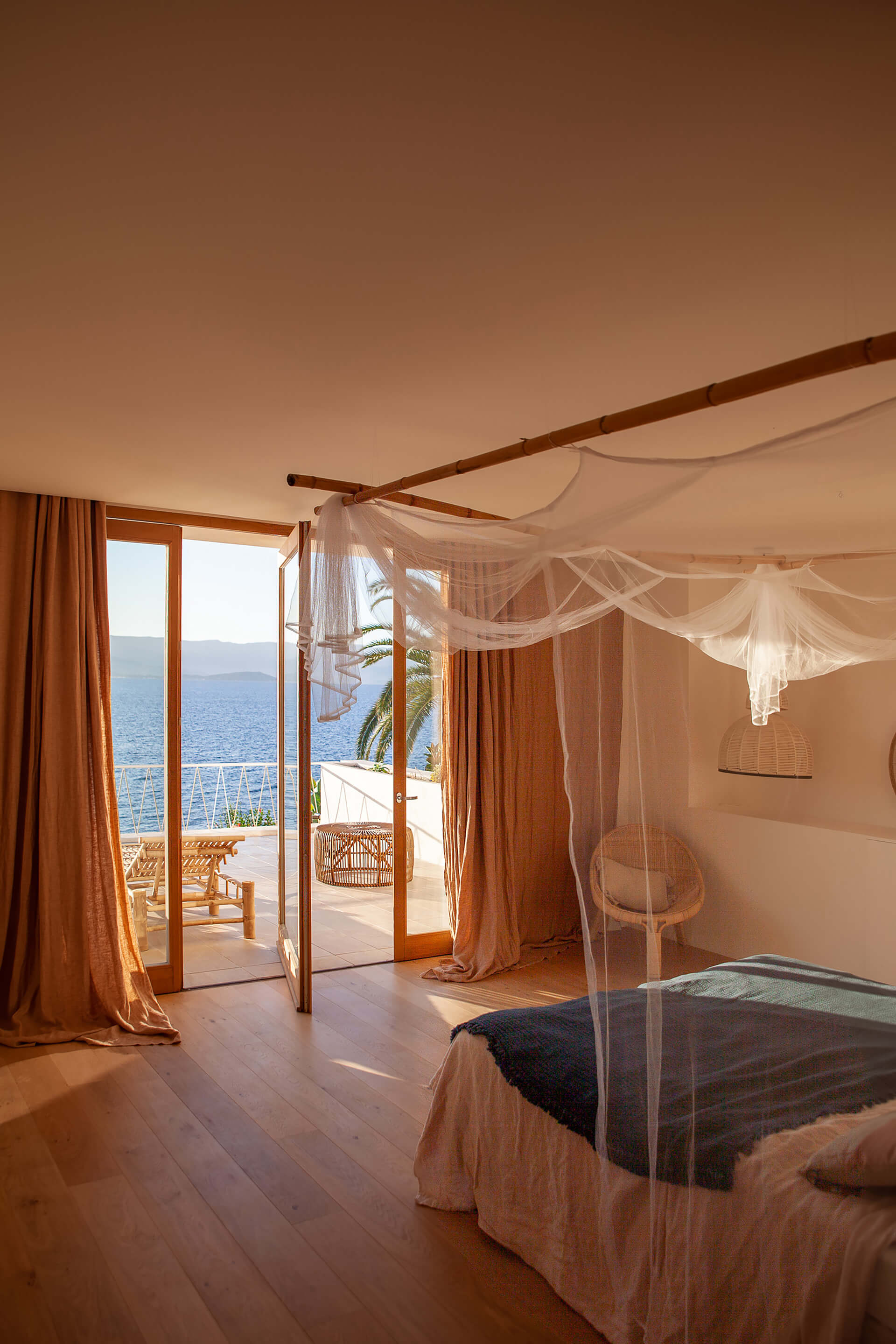 The warm coloured bedroom with views to the sea on the upper floor | Casa Santa Teresa in Corsica by Amelia Tavella Architects | STIRworld