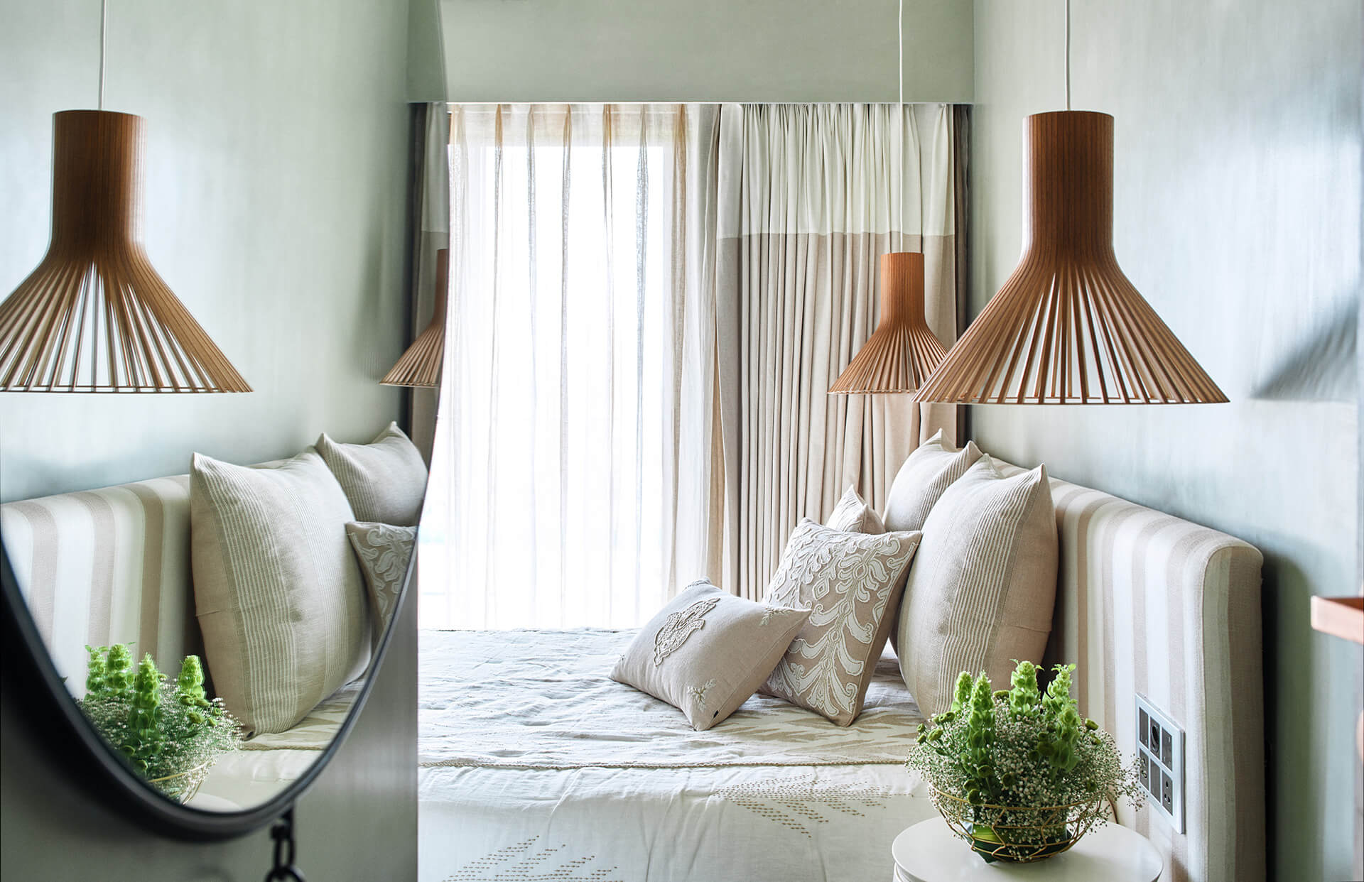 The guest room has a neutral coloured, striped bed with hanging lights from Secto Designs, sheets from Cotton and Satins | Ash Abode designed by FADD Studio | STIRworld