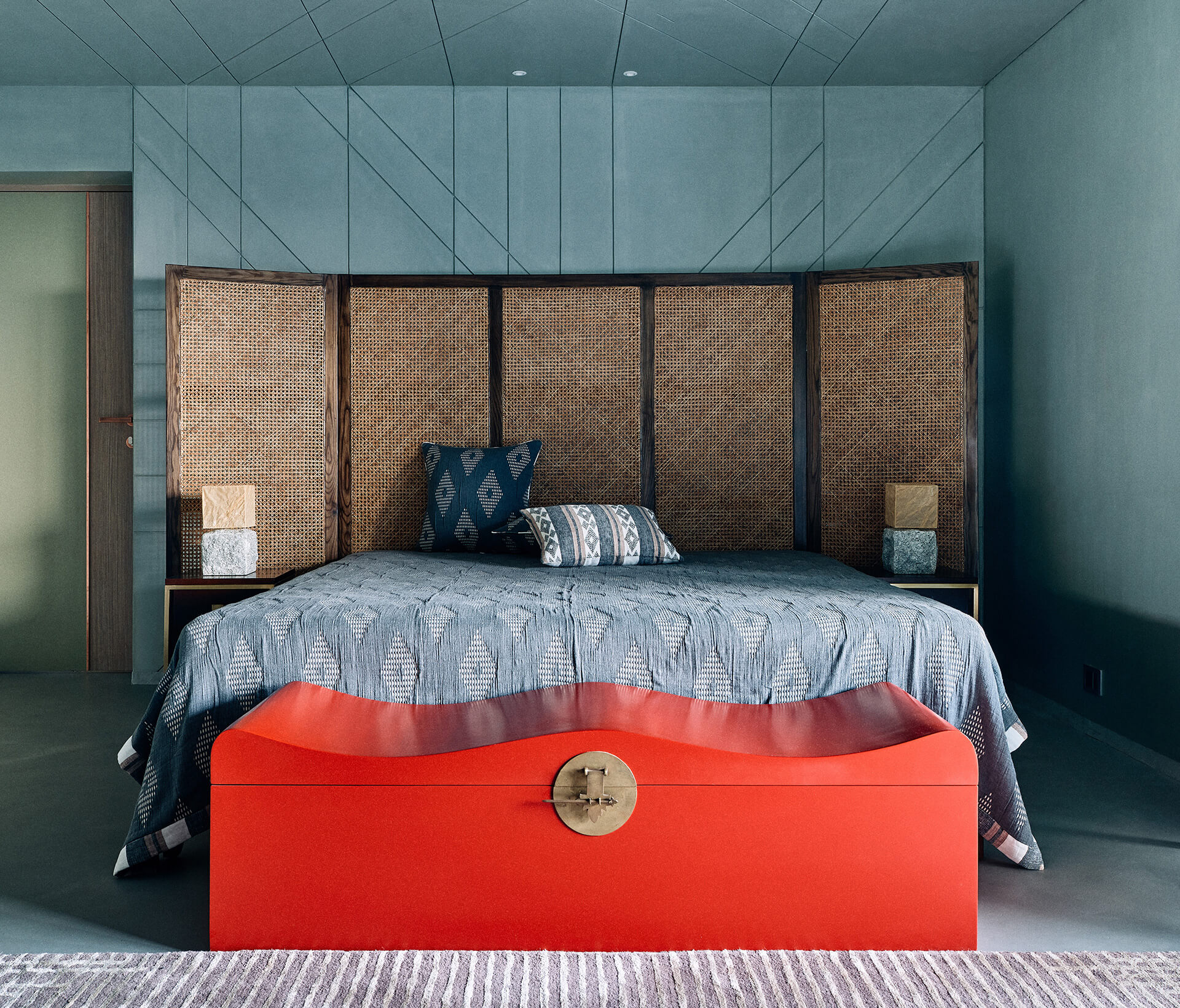 A winged cane bed customised from Magari sits in front of a grooved cement wall of the master bedroom | Ash Abode designed by FADD Studio | STIRworld