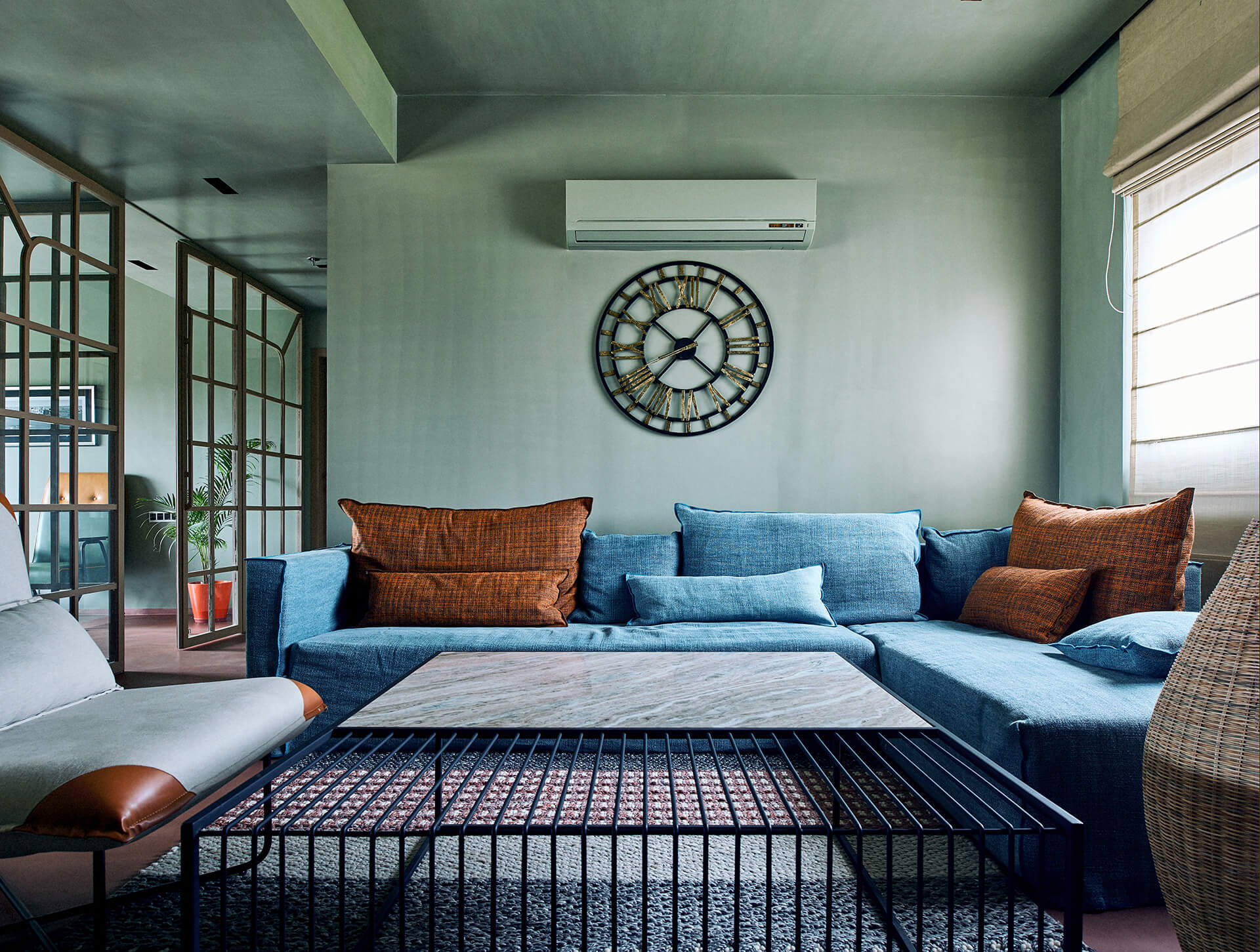 Family room – a blue Gervasoni sofa sits with customised Magari chairs and coffee table, Gervasoni cane floor lamps and a Collage clock | Ash Abode designed by FADD Studio | STIRworld
