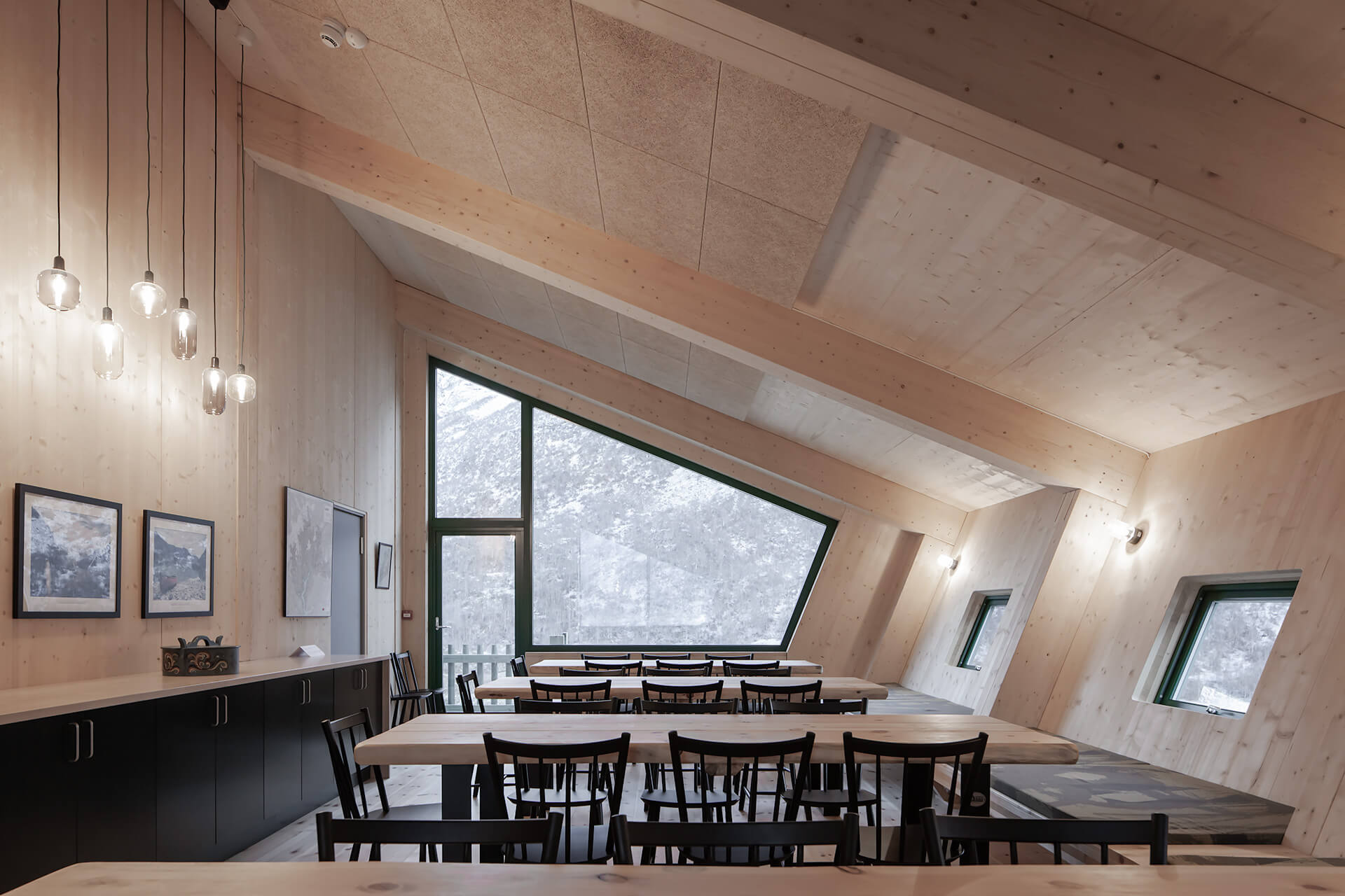The main cabin's communal dining area with exposed timber walls | Tungestølen Hiking Cabin by Snøhetta | STIRworld