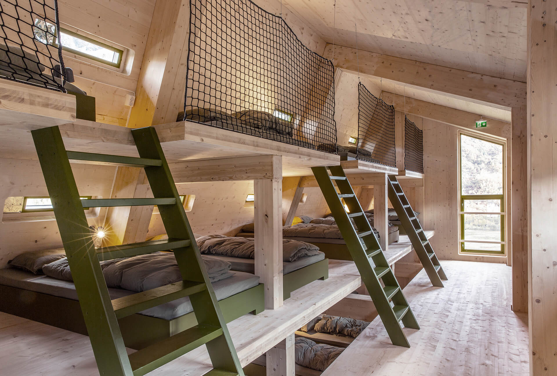 Olive green ladders used to access bunk beds inside Tungestølen | Tungestølen Hiking Cabin by Snøhetta | STIRworld