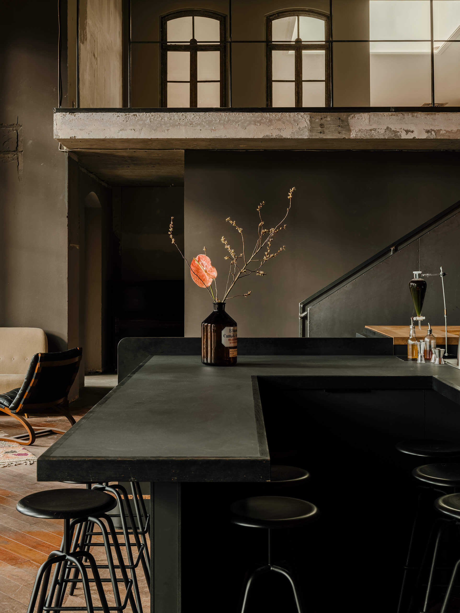 The solid black bar countertop with black stools | KINK Bar and Restaurant by Oliver Mansaray and Daniel Scheppan | STIRworld