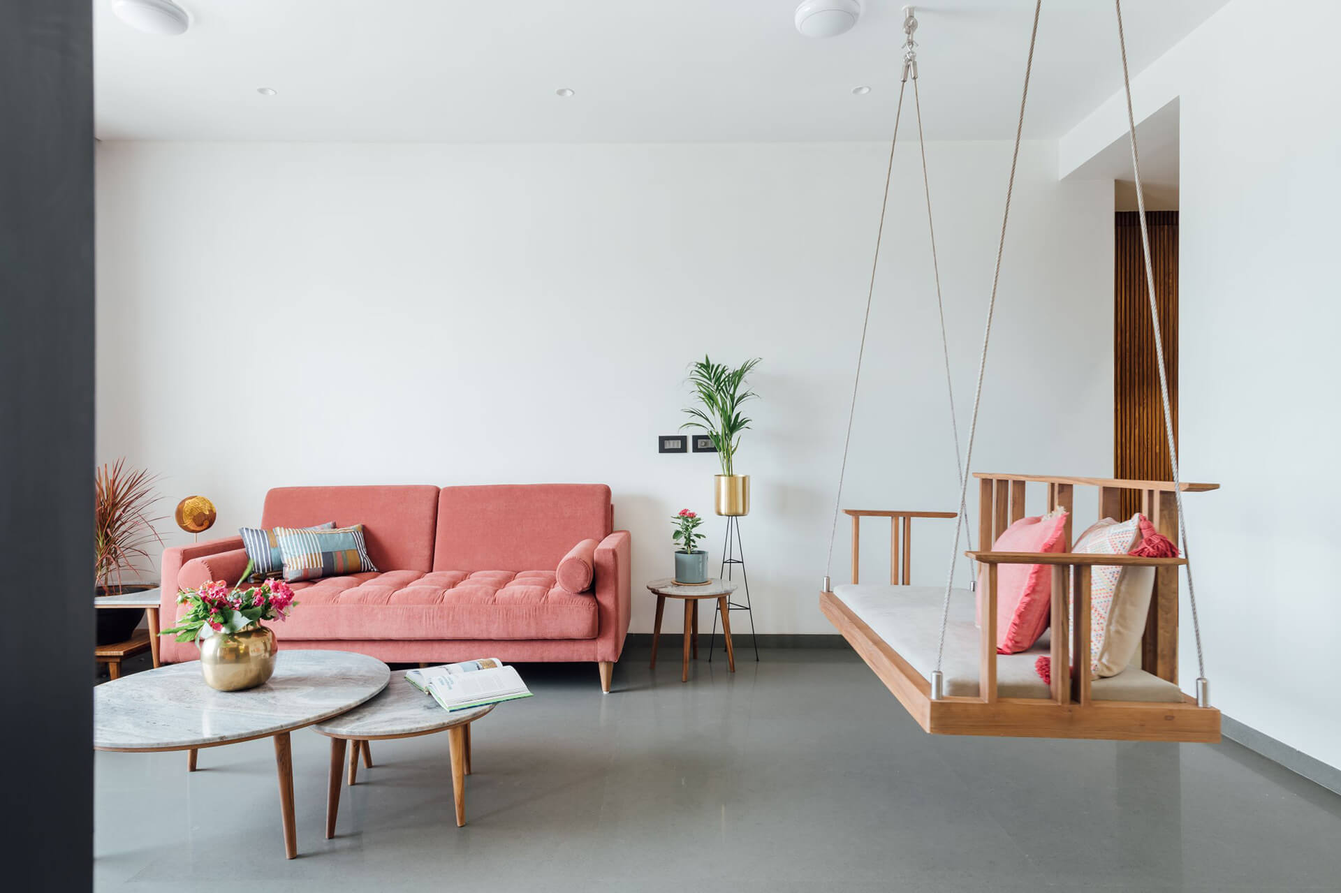 Living room with coral pink cushions and a swing | Neogenesis + Studi0261 | India | STIRworld