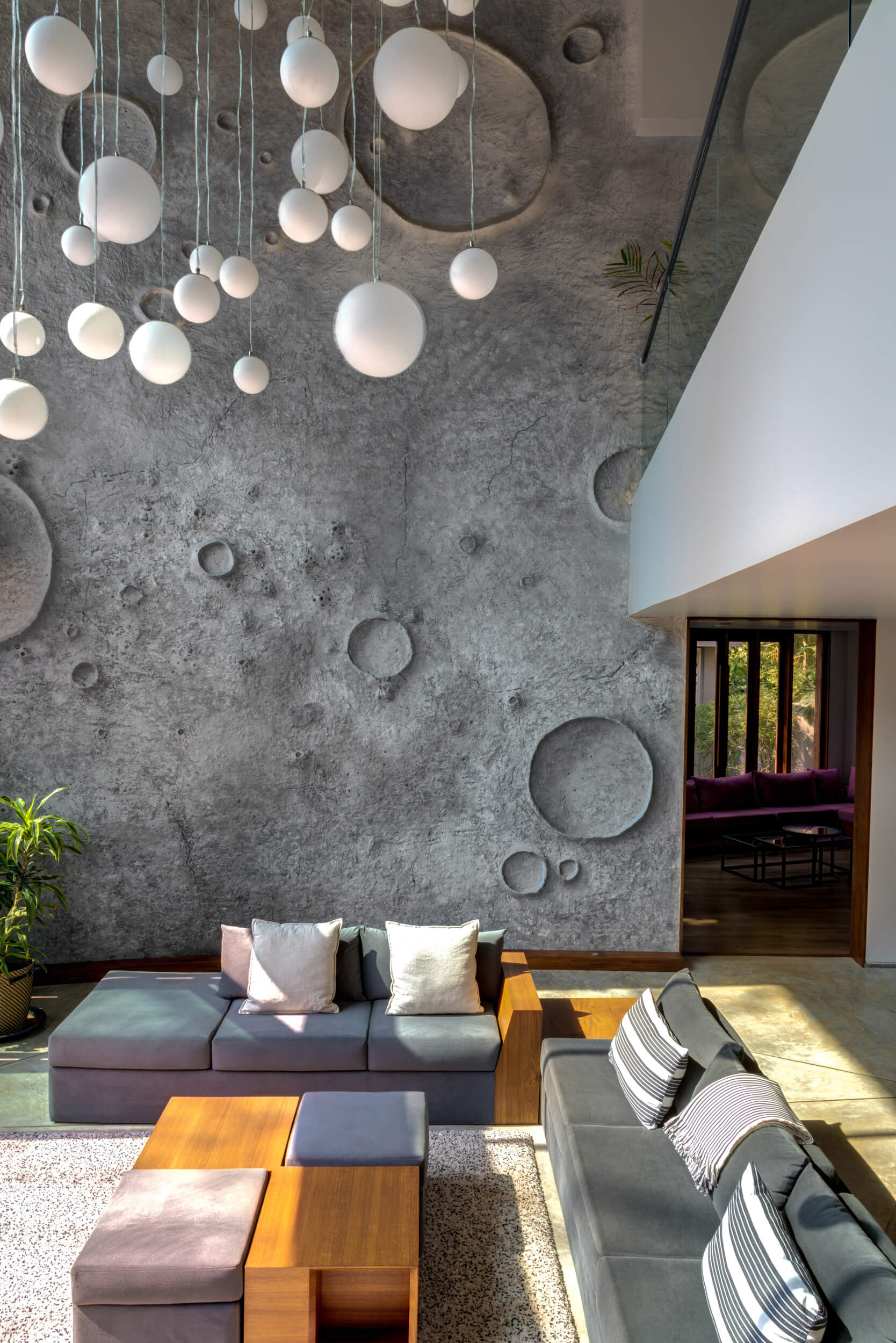 Crater like textured wall and chandelier in Lua's living room | Lua and Terra Si-oul villas by Kriss Real Estate and SAV architects | STIRworld