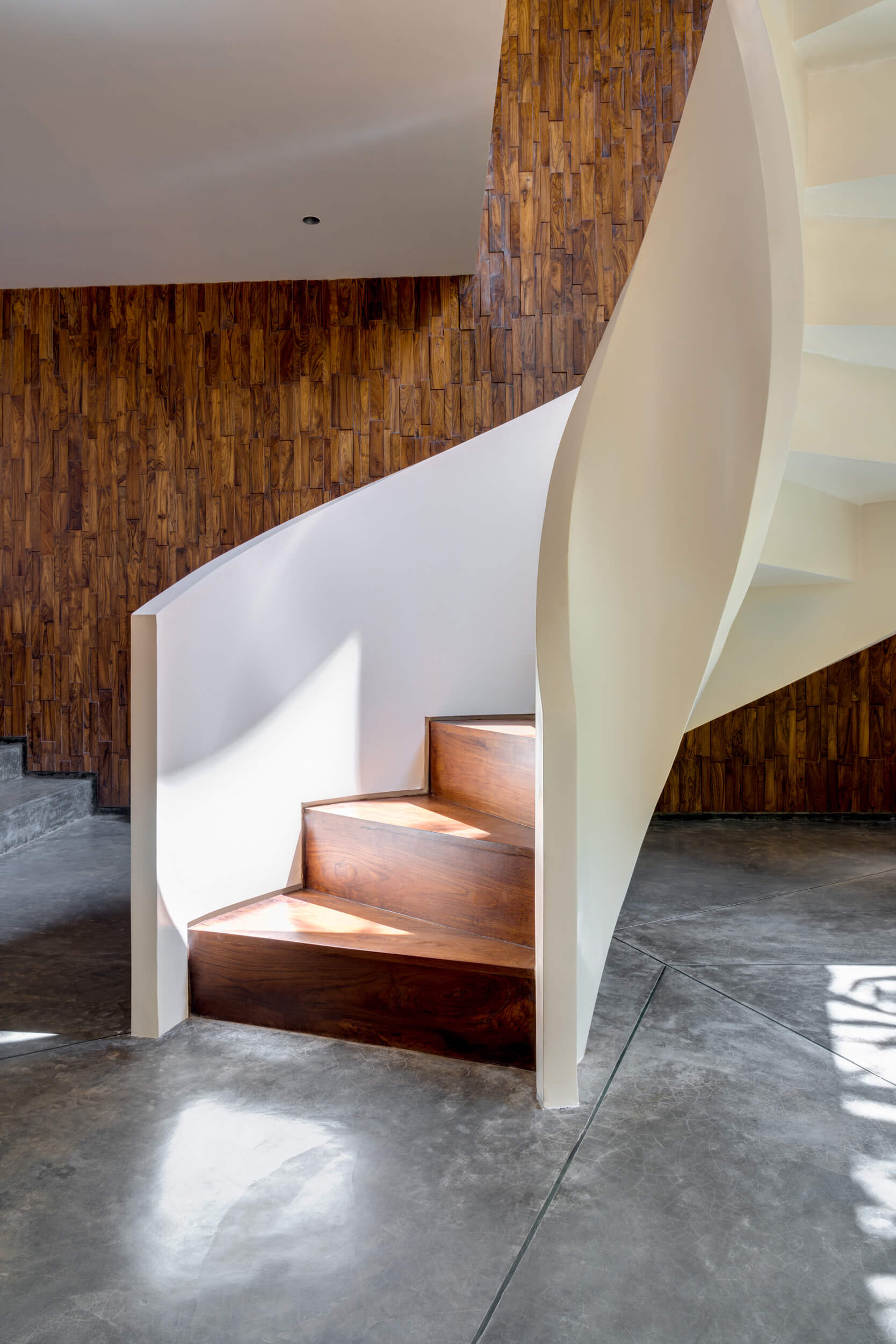Interior view showing teak wood walls and spiral staircase of Terra house | Lua and Terra Si-oul villas by Kriss Real Estate and SAV architects | STIRworld