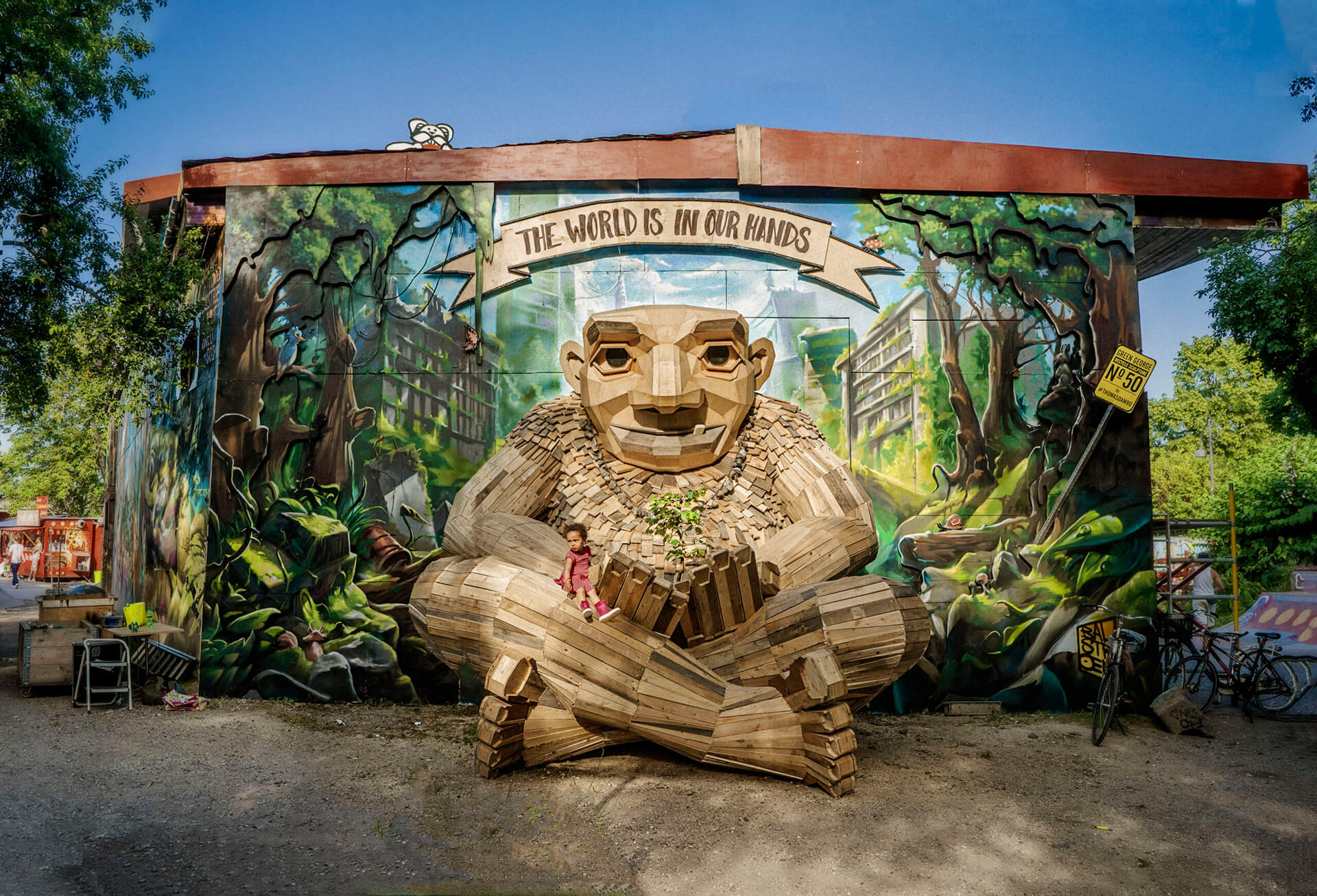 Green George was built with trashed wood from Christiania's (Oslo's) garbage disposal. The mural was done in collaboration with Rasmus Balstrøm | Green George by Thomas Dambo| STIRworld