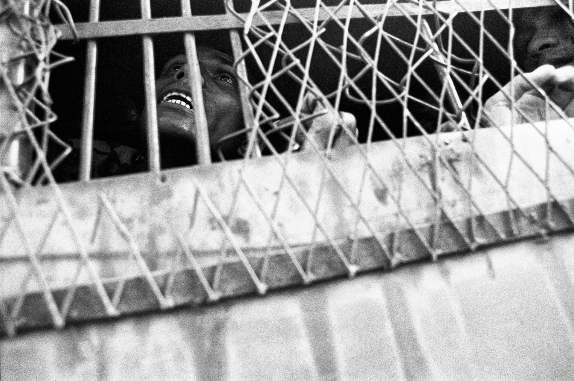 A student who had been picked up in a massive police raid, reaches out for help from the prison van | Shahidul Alam | World Photography Day | STIRworld