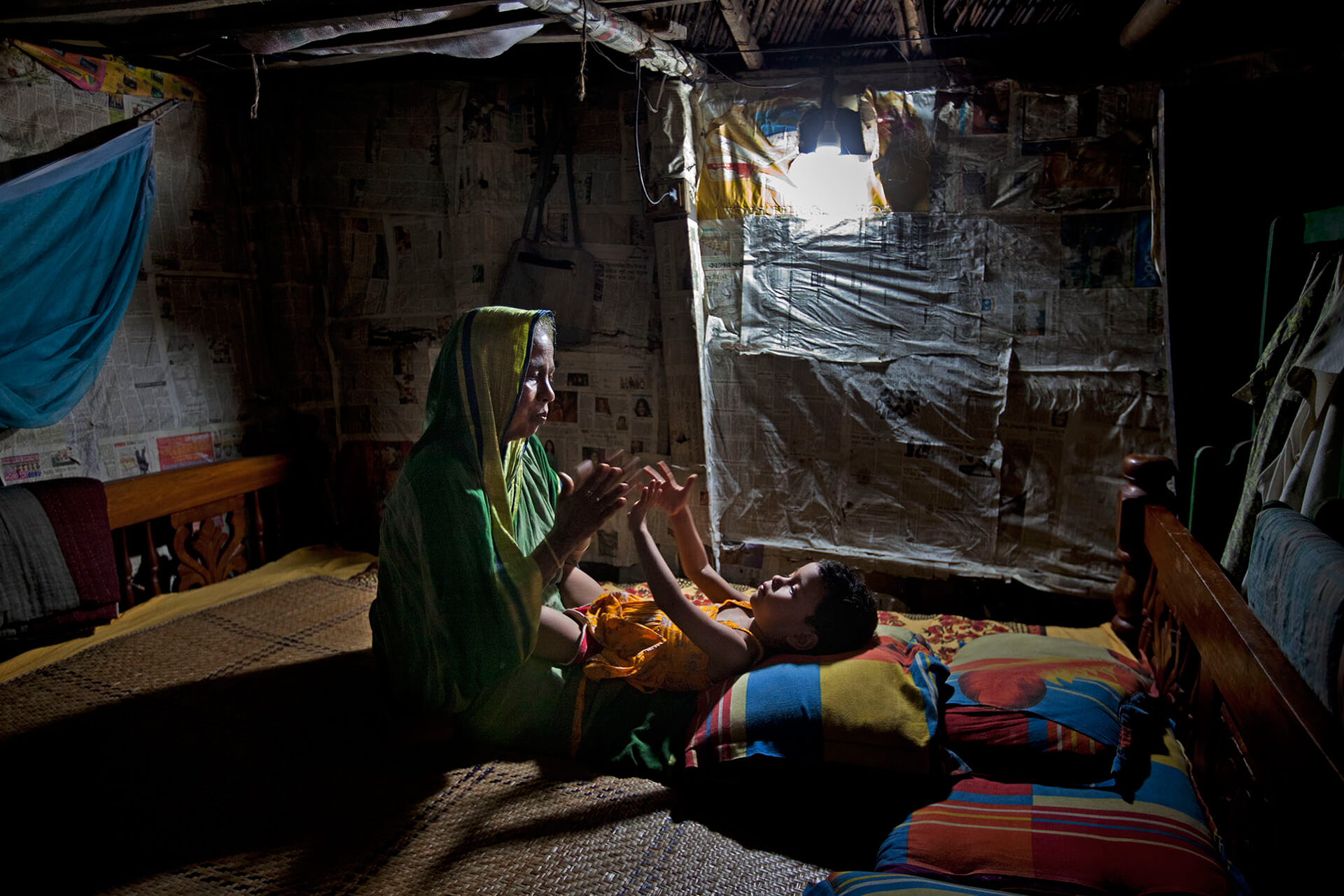 Shofiqul Islam was conned by traffickers and stranded in Libya without a job. Shofiq's mother playing with her granddaughter | Shahidul Alam | World Photography Day | STIRworld
