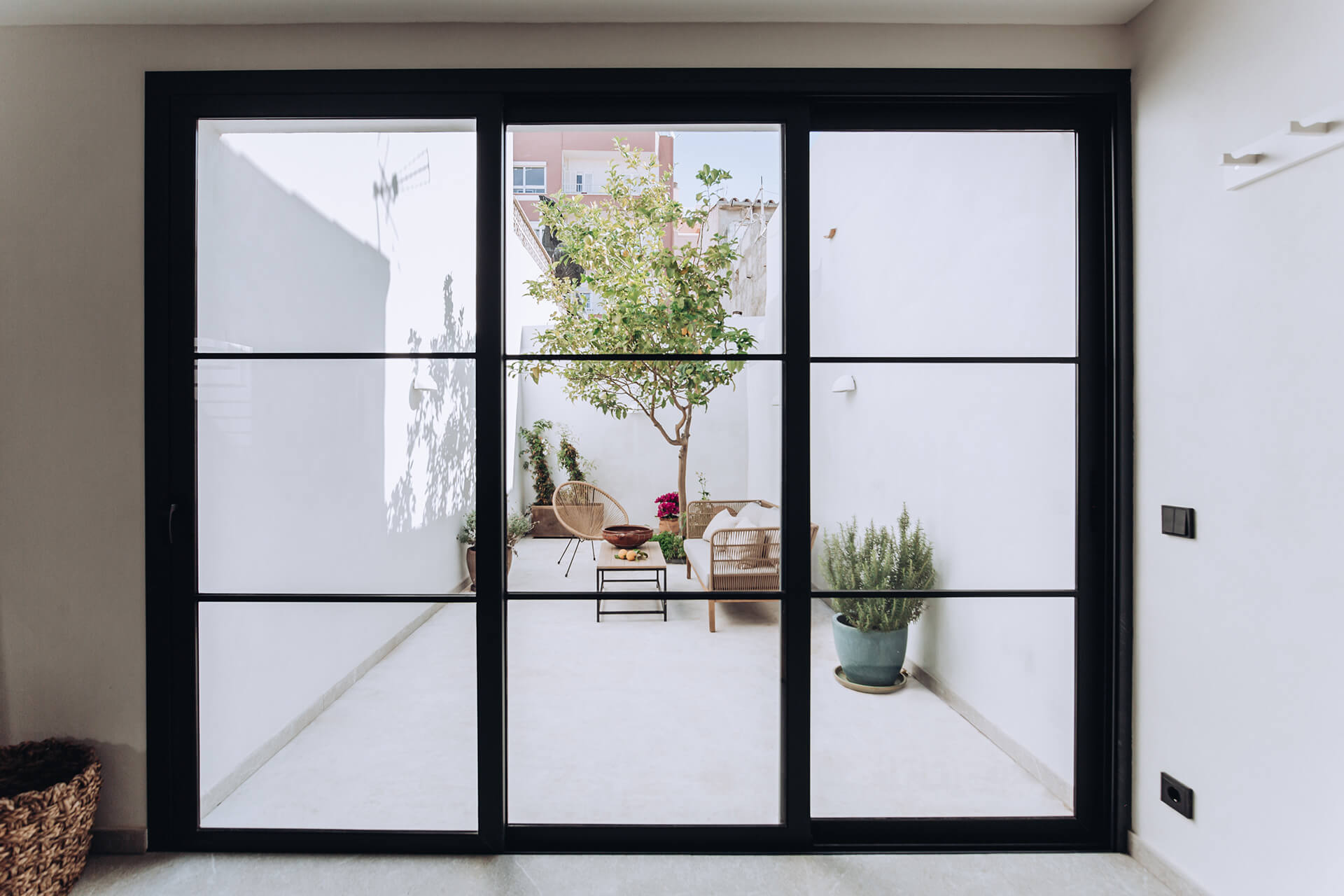 A large sliding door opens into the patio, the black frame reminiscent of the client's Scandinavian roots| Portixol House by PMA Studio | STIRworld