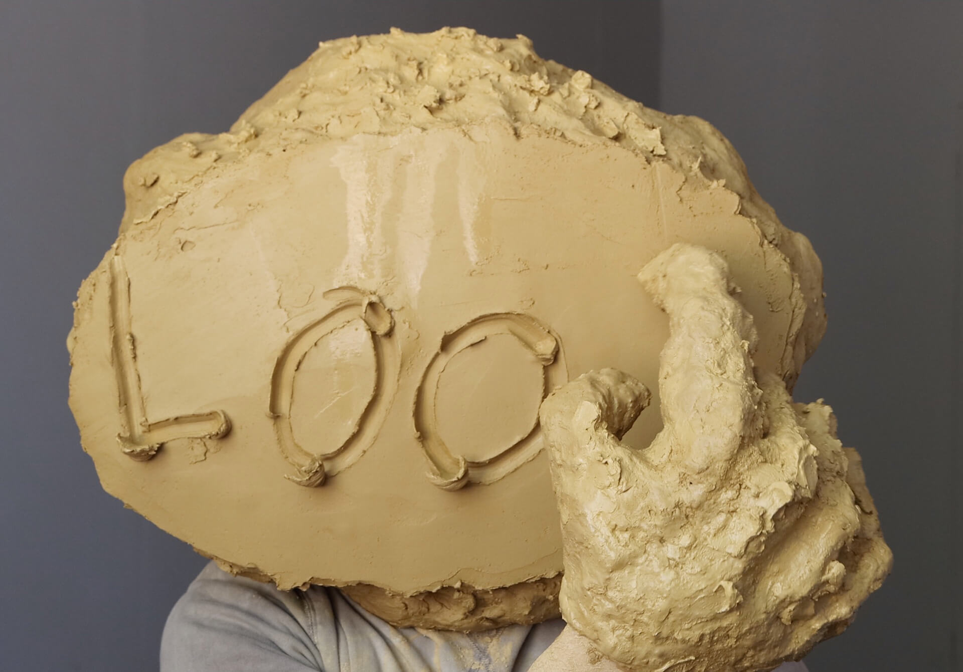 Artist William Cobbing performing inside a clay head| STIRworld