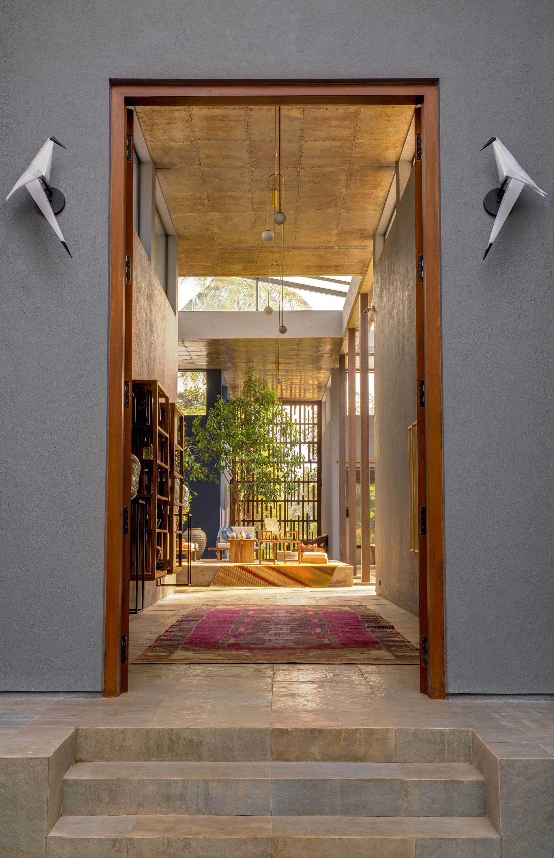 The entrance door that frames views towards the courtyard | Uminoya – Weekend home in Alibaug | Clay Architecture and Interiors | STIRworld