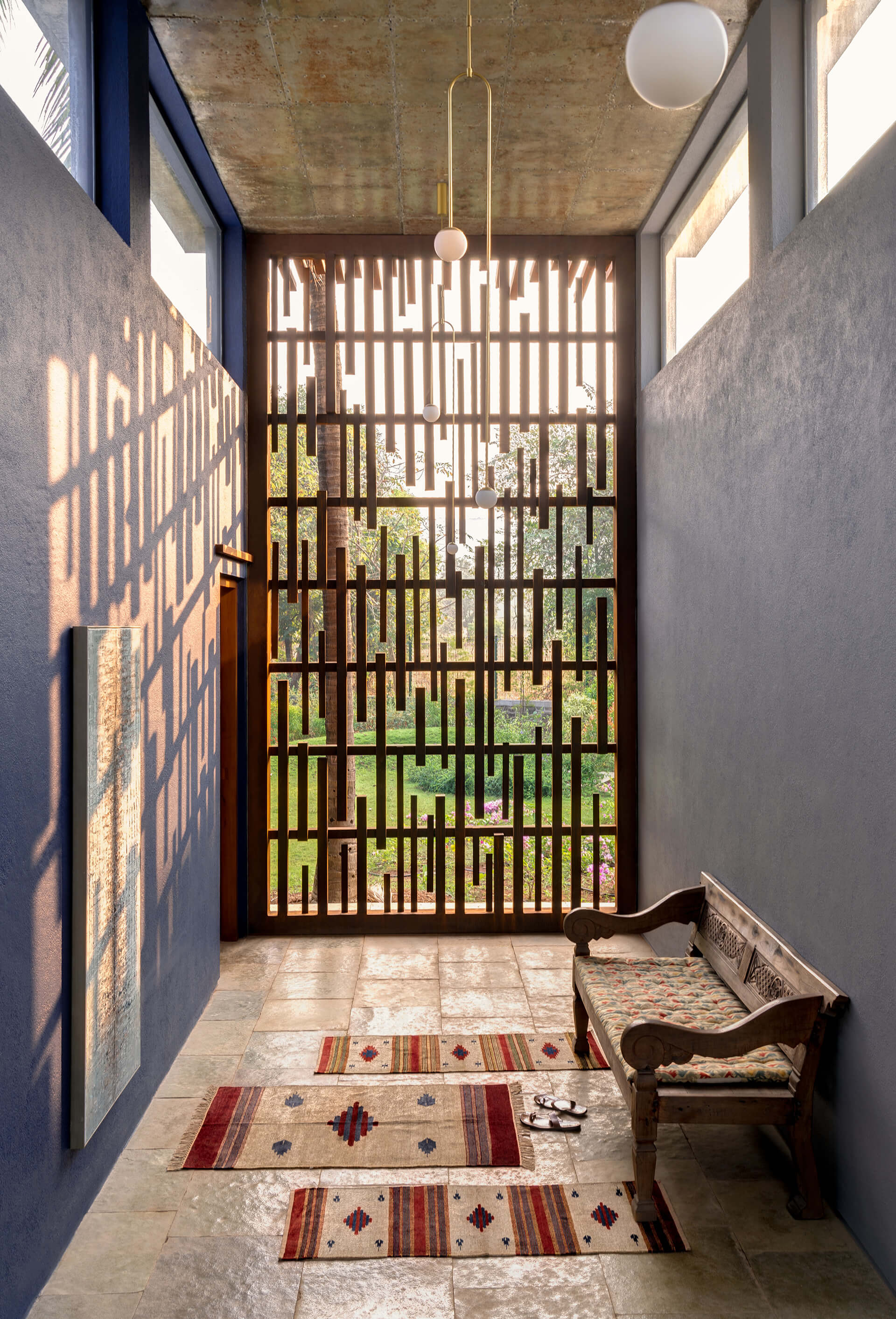 The quiet spaces in the home with a wooden screen showing the subtle and contemporary hues used in the design | Uminoya – Weekend home in Alibaug | Clay Architecture and Interiors | STIRworld