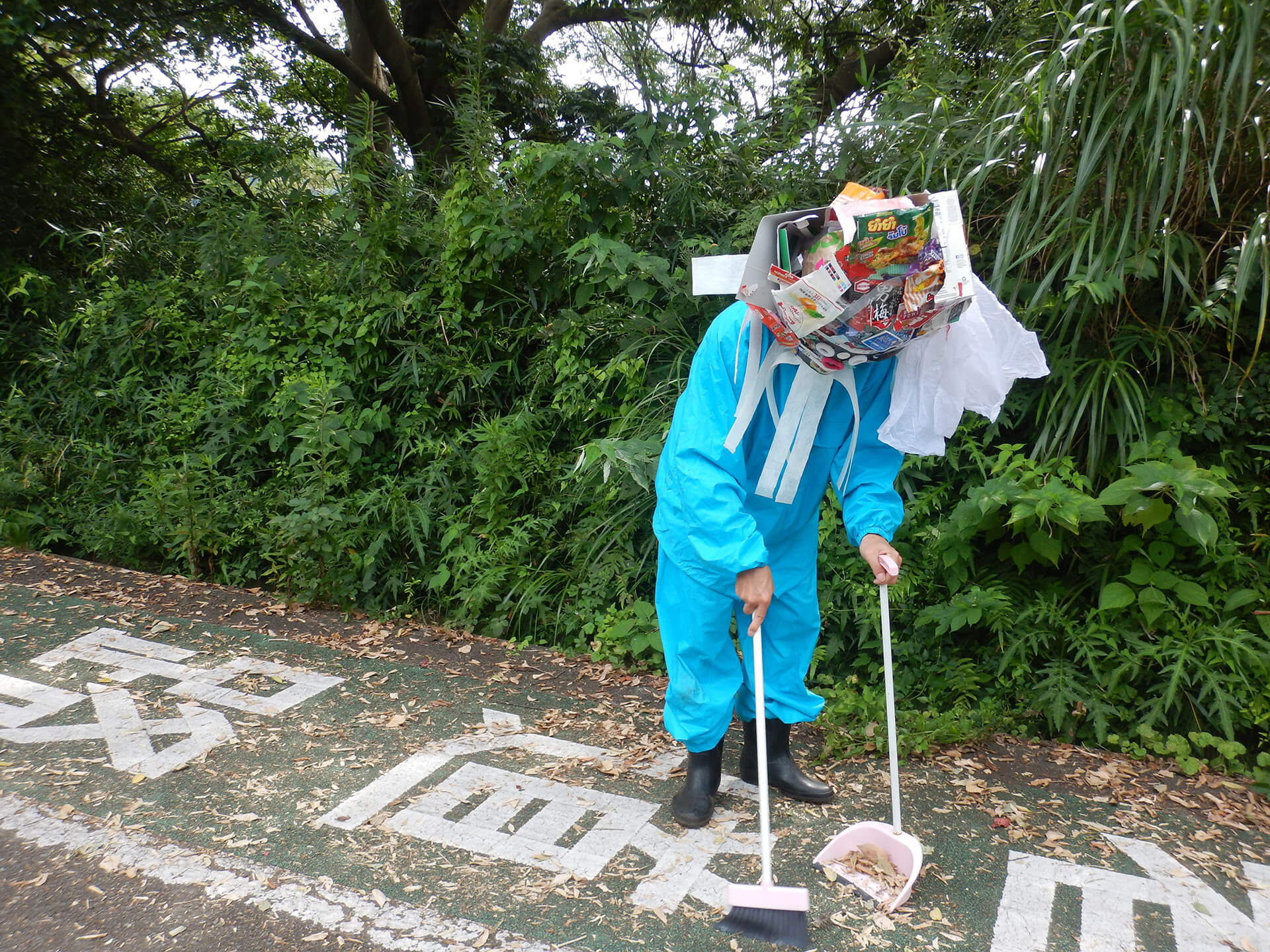 A participant of Broom Stars collecting garbage from the road as part of the project | Broom Stars by Masaru Iwai at Yokohama Triennale 2020| STIRworld