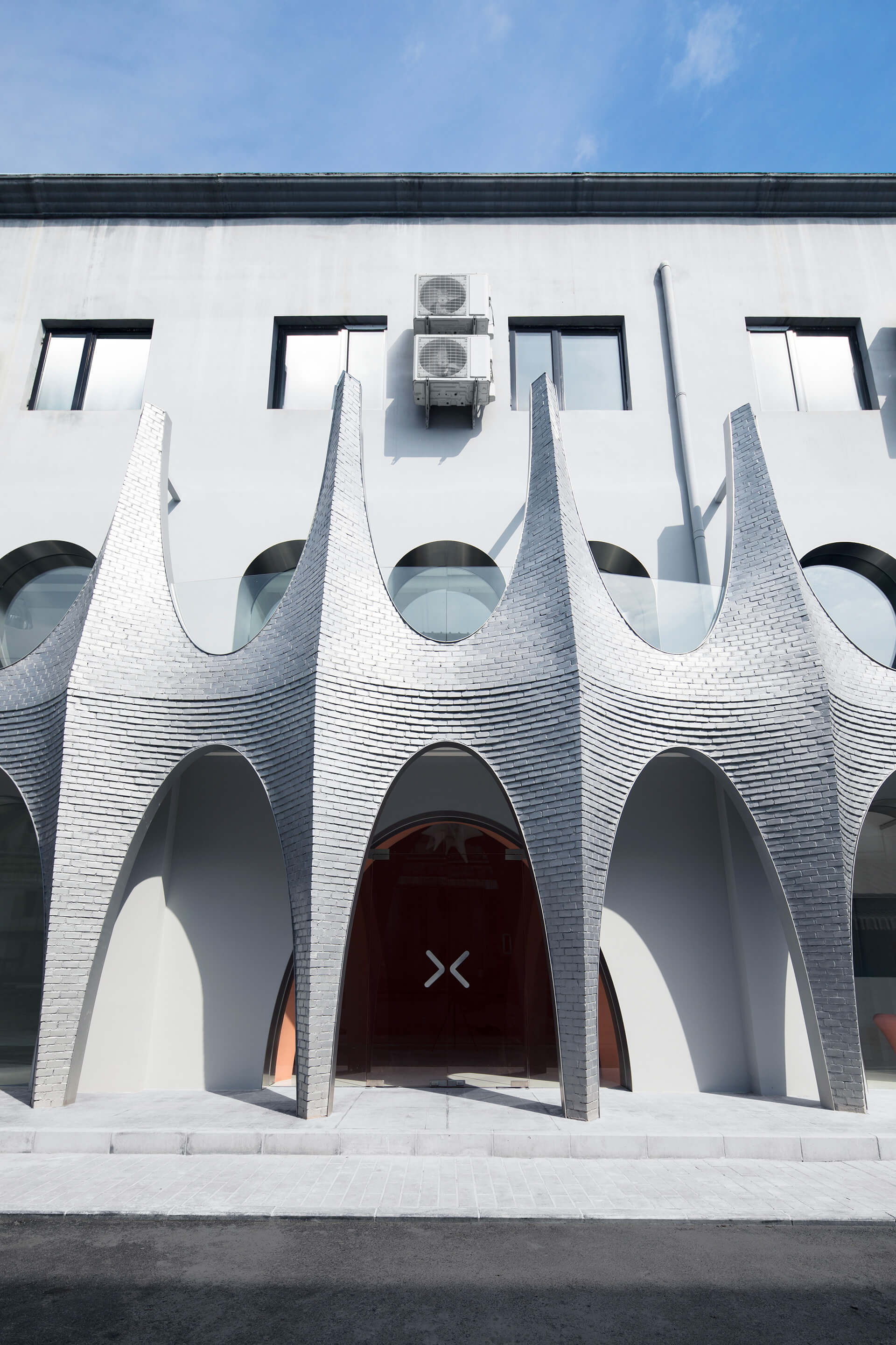 The new facade forms space for a second-floor balcony | Masquerade by 123 Architects | STIRworld