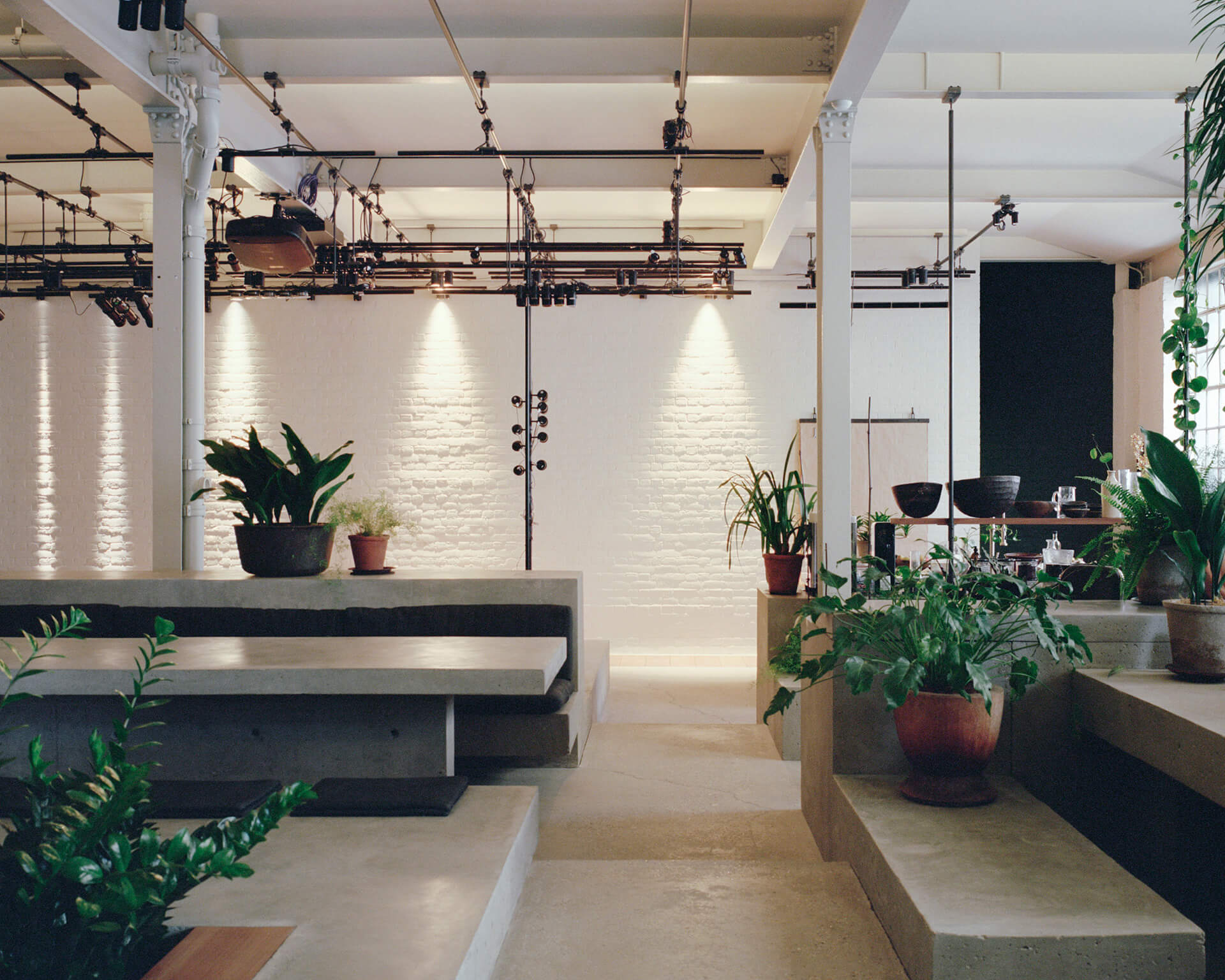 Shades of grey, plants and climbers contrast the largely white office | PSLab Headquarters designed by James Plumb | STIRworld