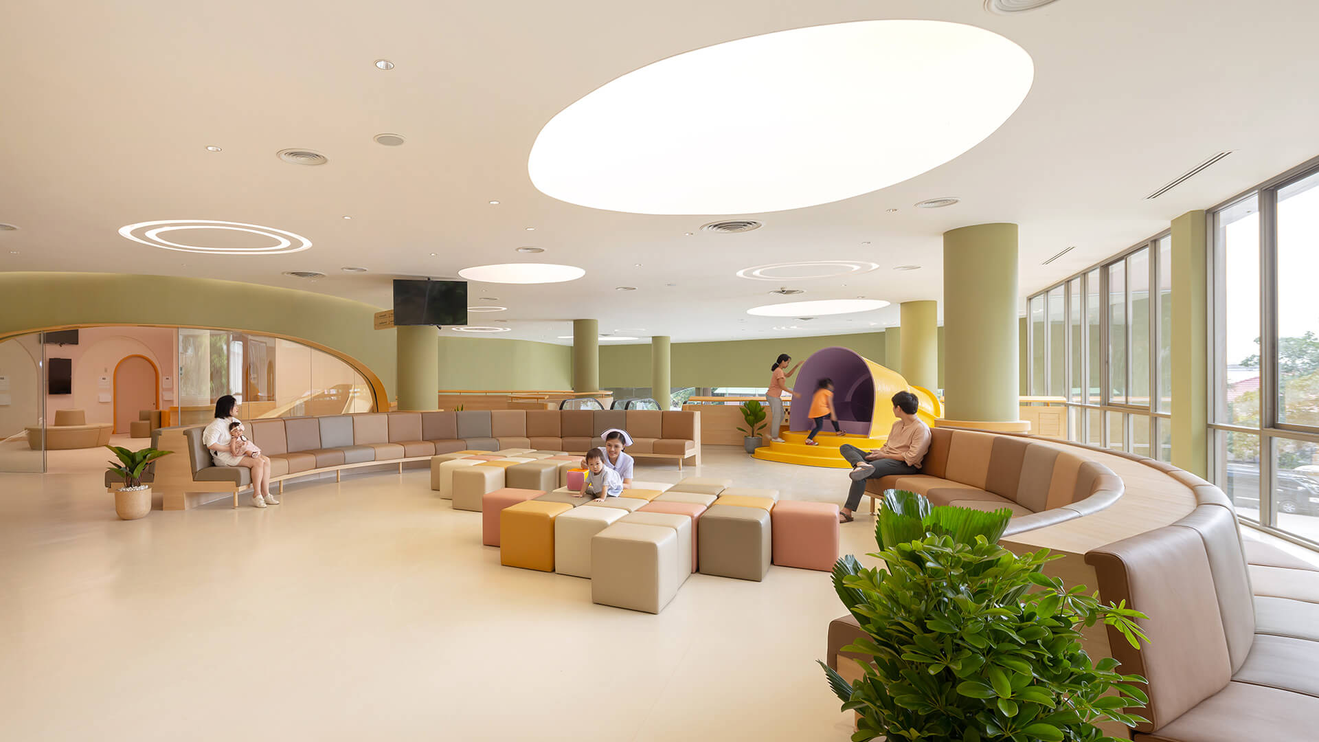 Rounded furniture and the yellow slider on the first level | EKH Children's Hospital by Integrated Field | STIRworld