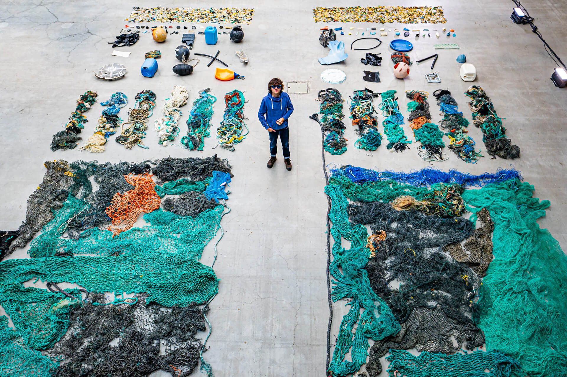 Boyan Slat standing with plastic caught during their second collection campaign in 2019| The Ocean Cleanup Sunglasses | STIRworld