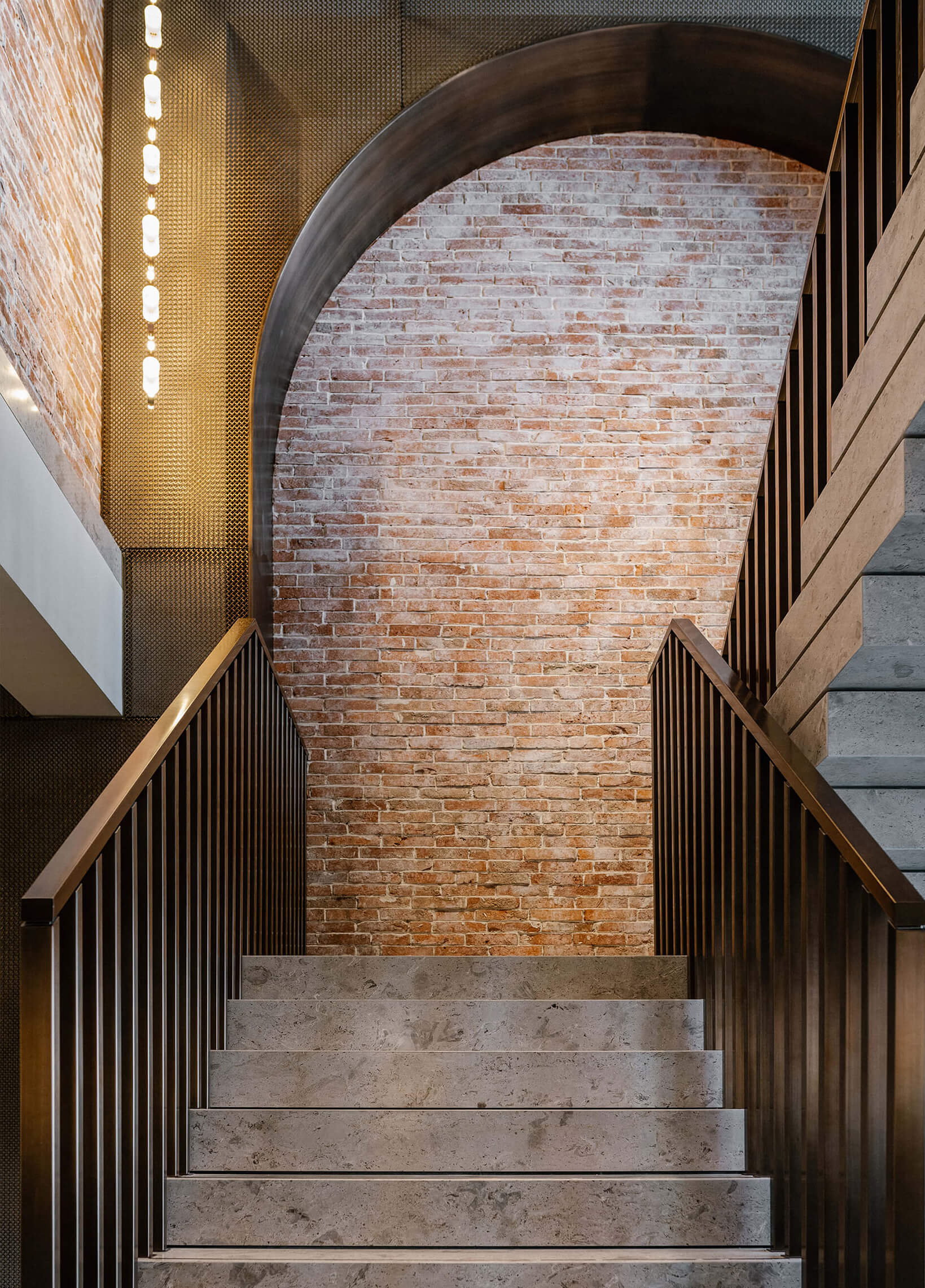 Bronze arches and double height stairway sit against exposed brick walls | House of Madison designed by via. | STIRworld