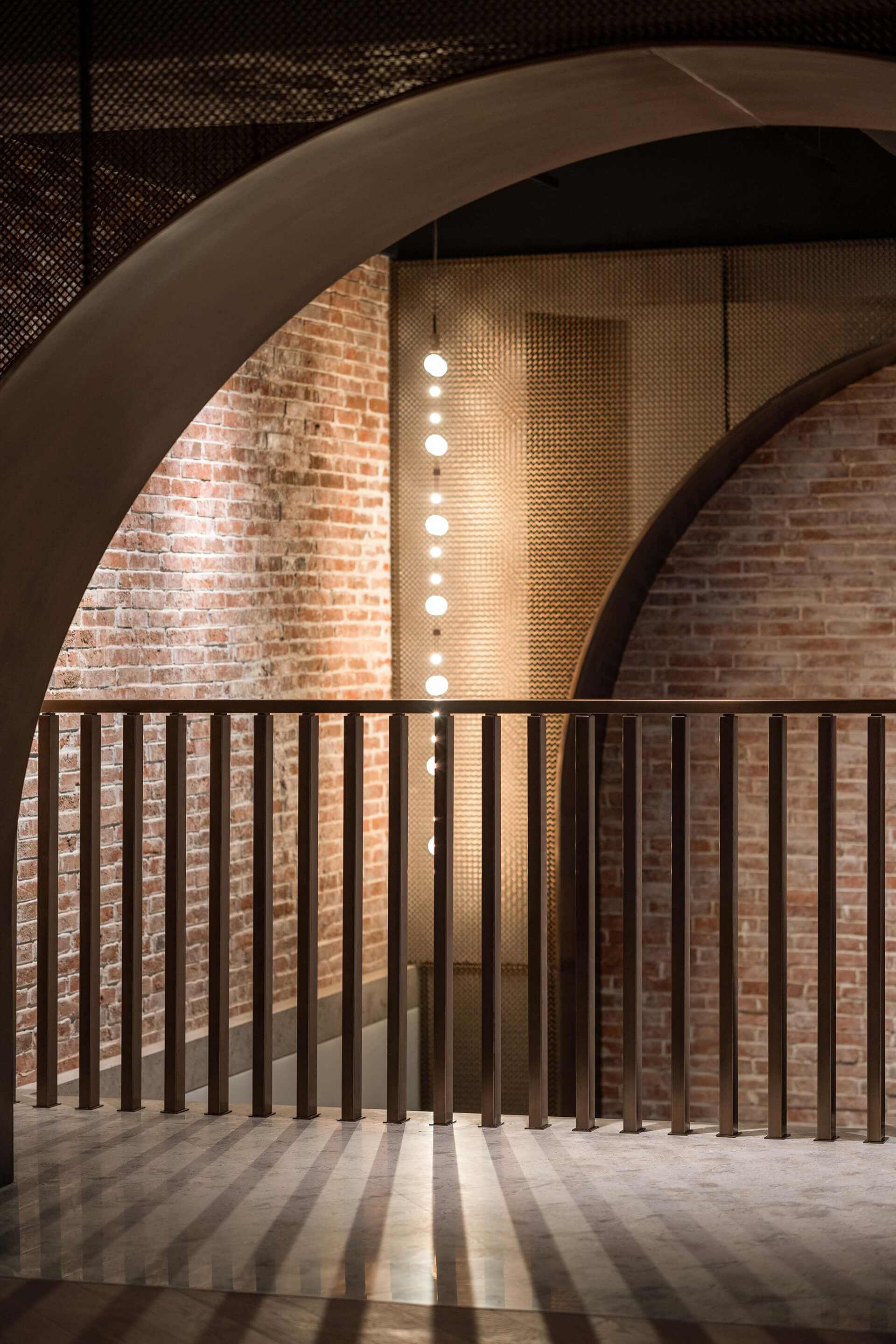 View of the stairway and wire mesh, bronze arch | House of Madison designed by via. | STIRworld